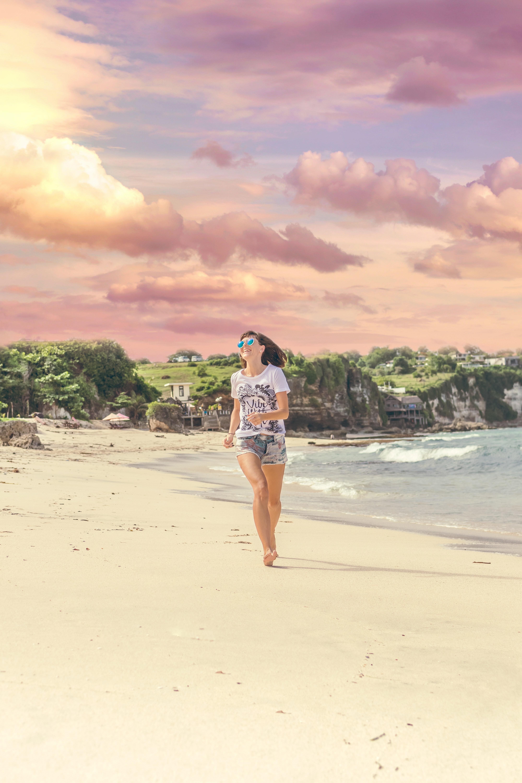 Smiling woman walking barefood on seashore near houses photo