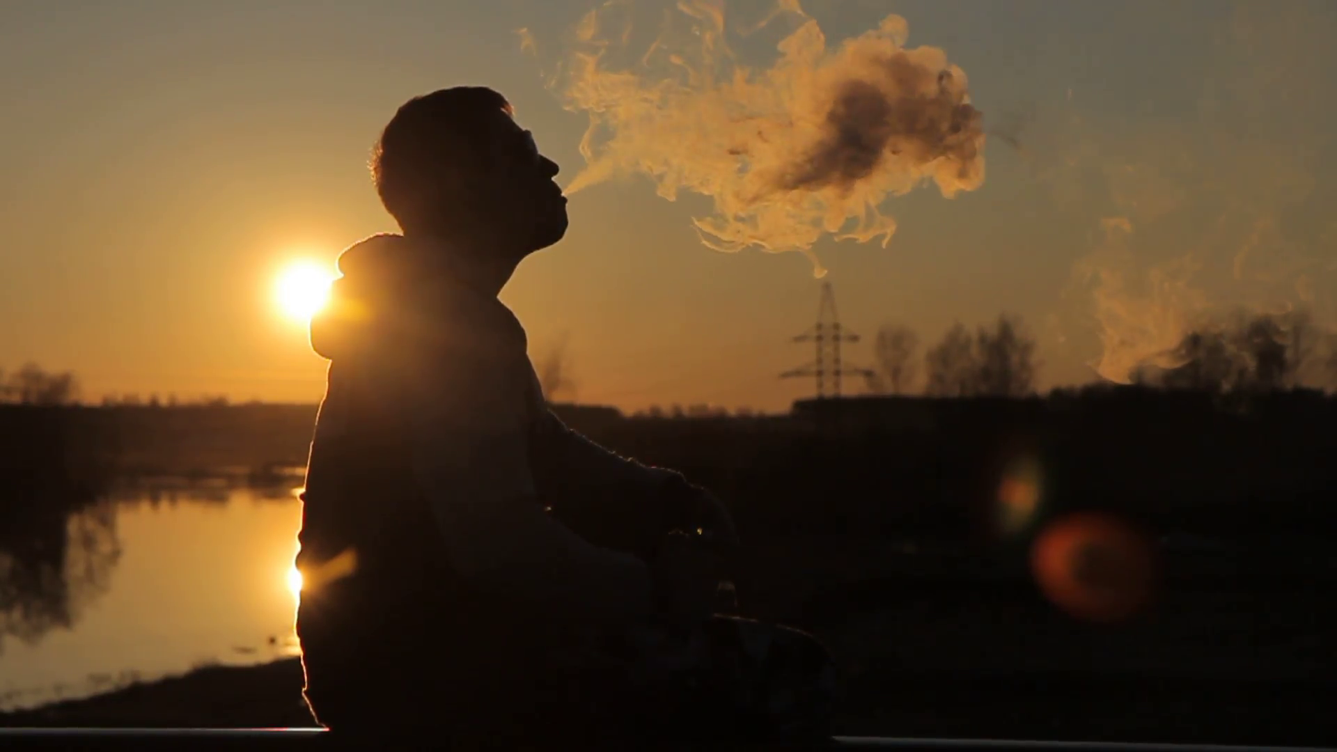 a young man at sunset smoking electronic cigarette Stock Video ...
