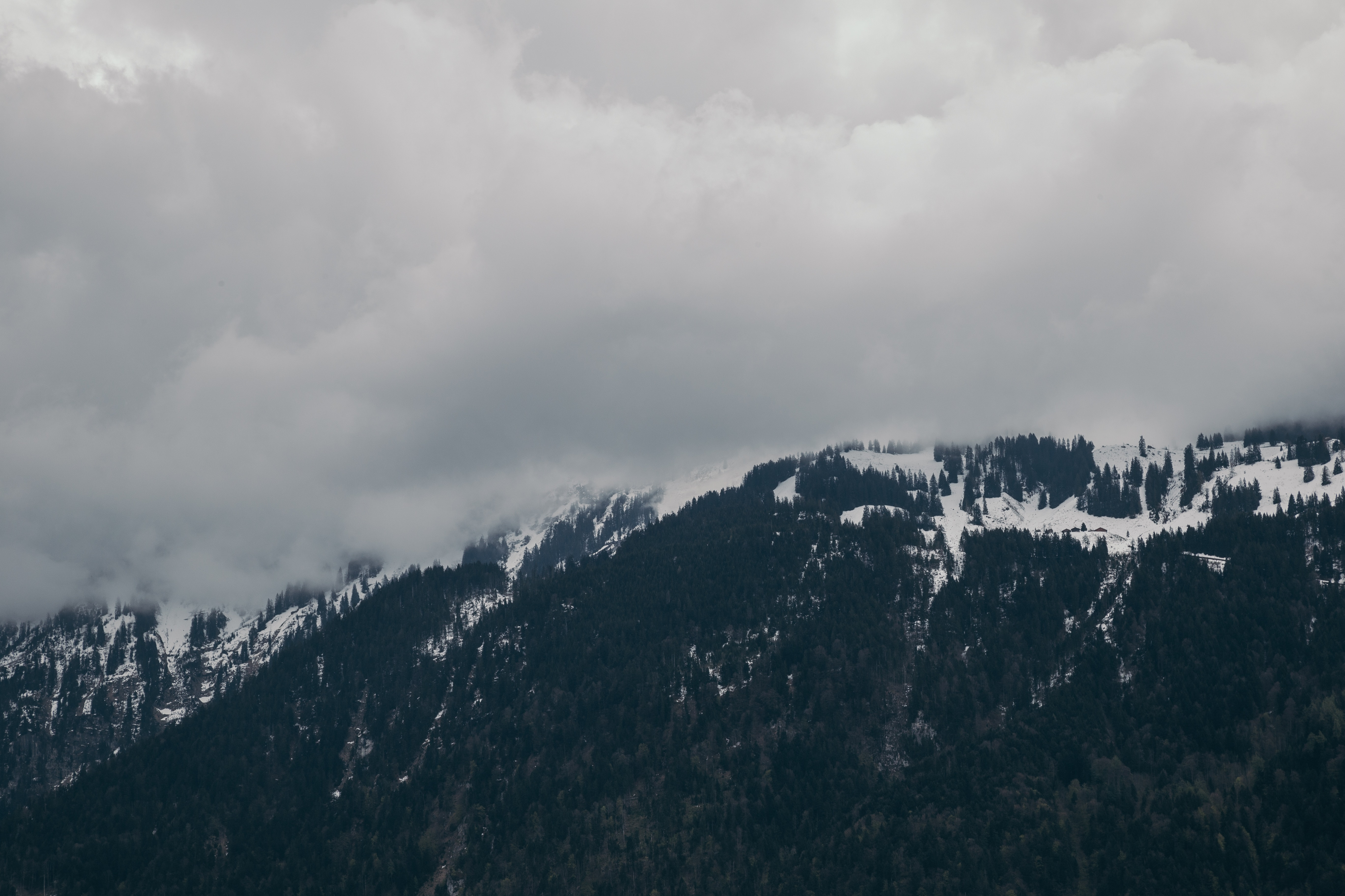 Snow-capped mountain under cloudy sky photo