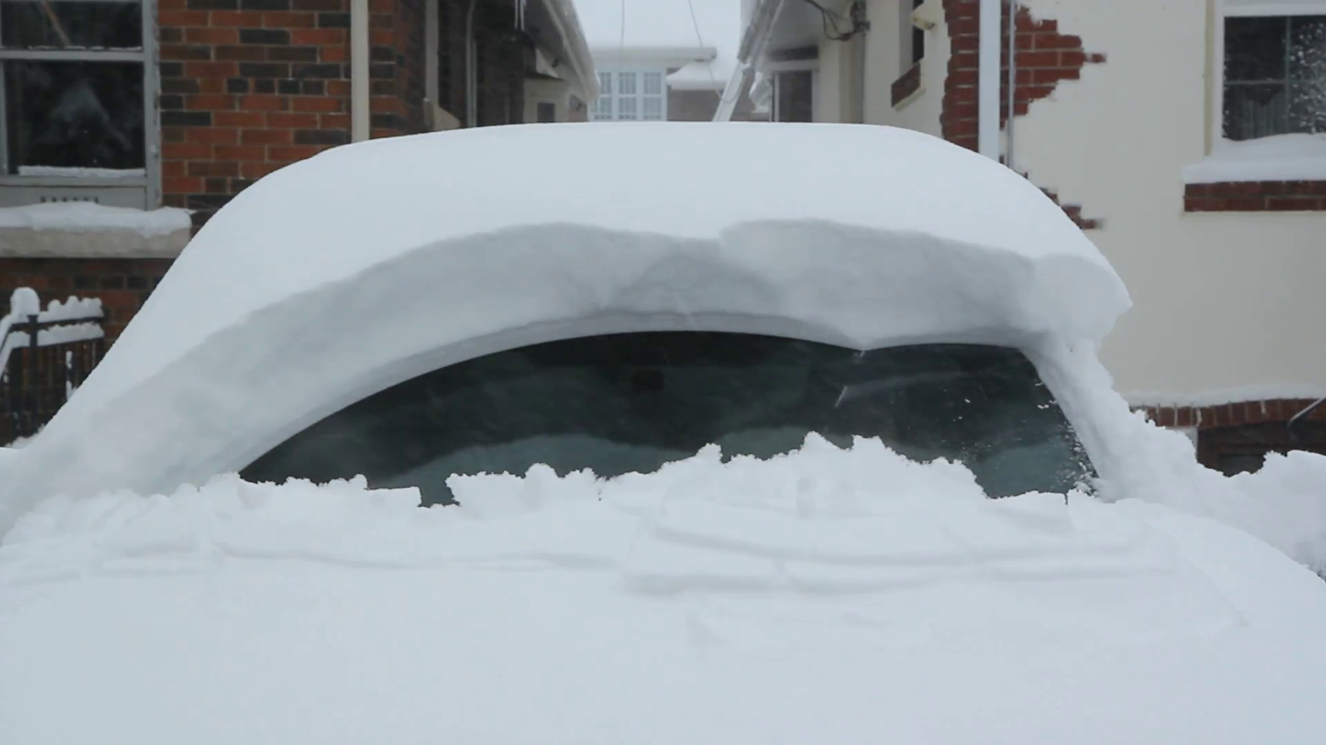 Starting a snow covered car. Wipers working to clear thick snow ...