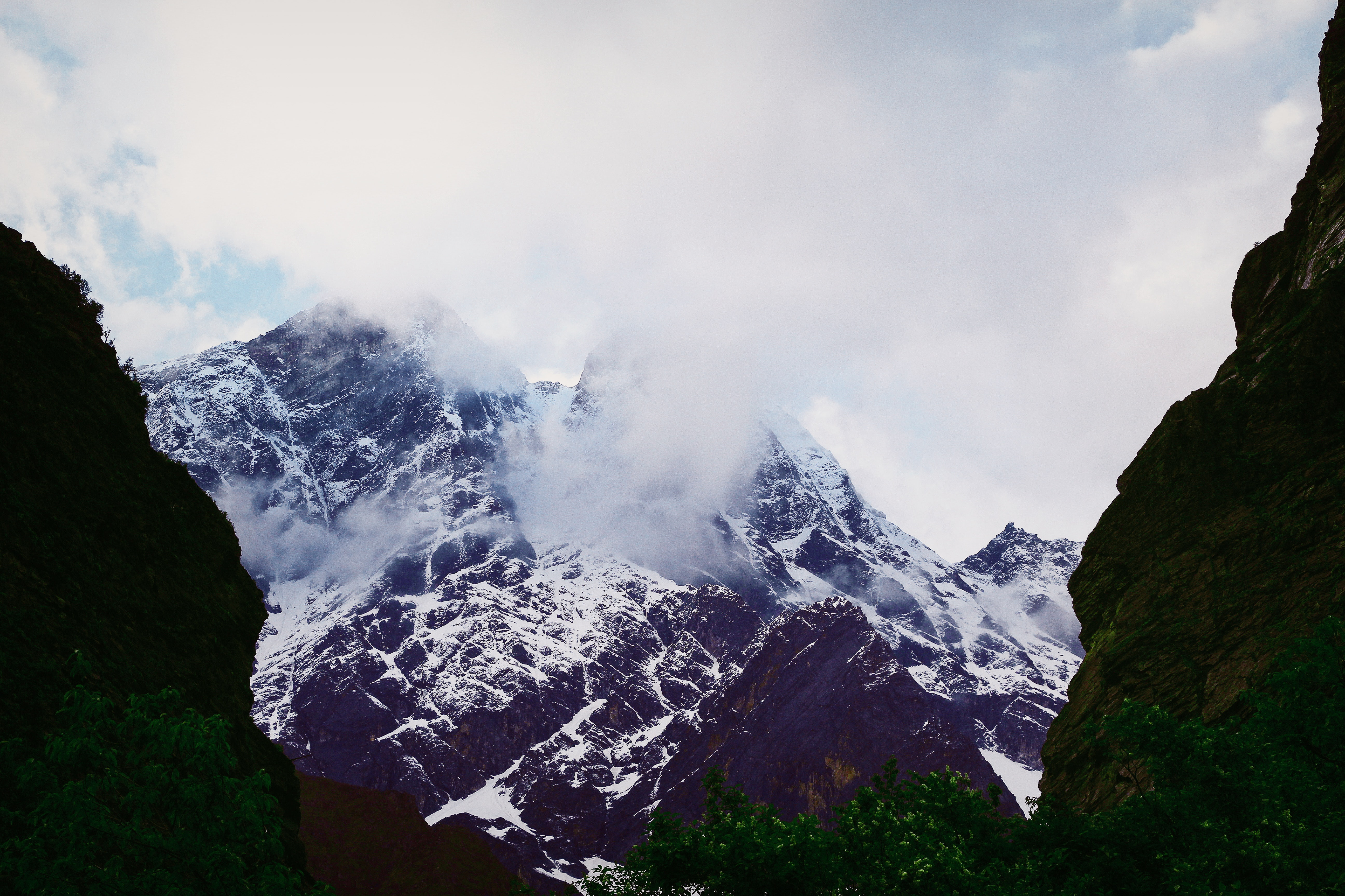 Snow covered mountain under cloudy sky photo