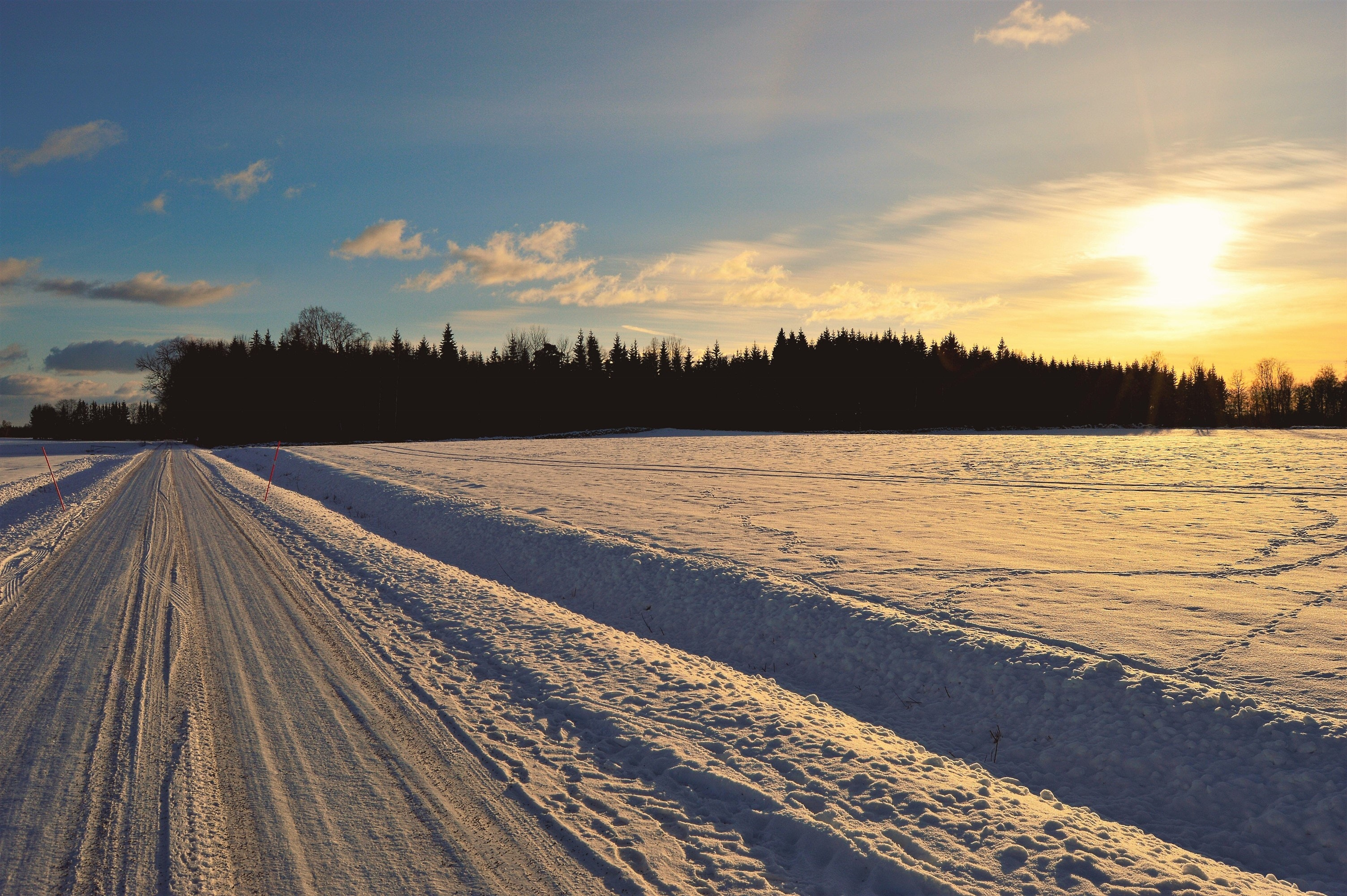 Snow covered road during golden hour photo