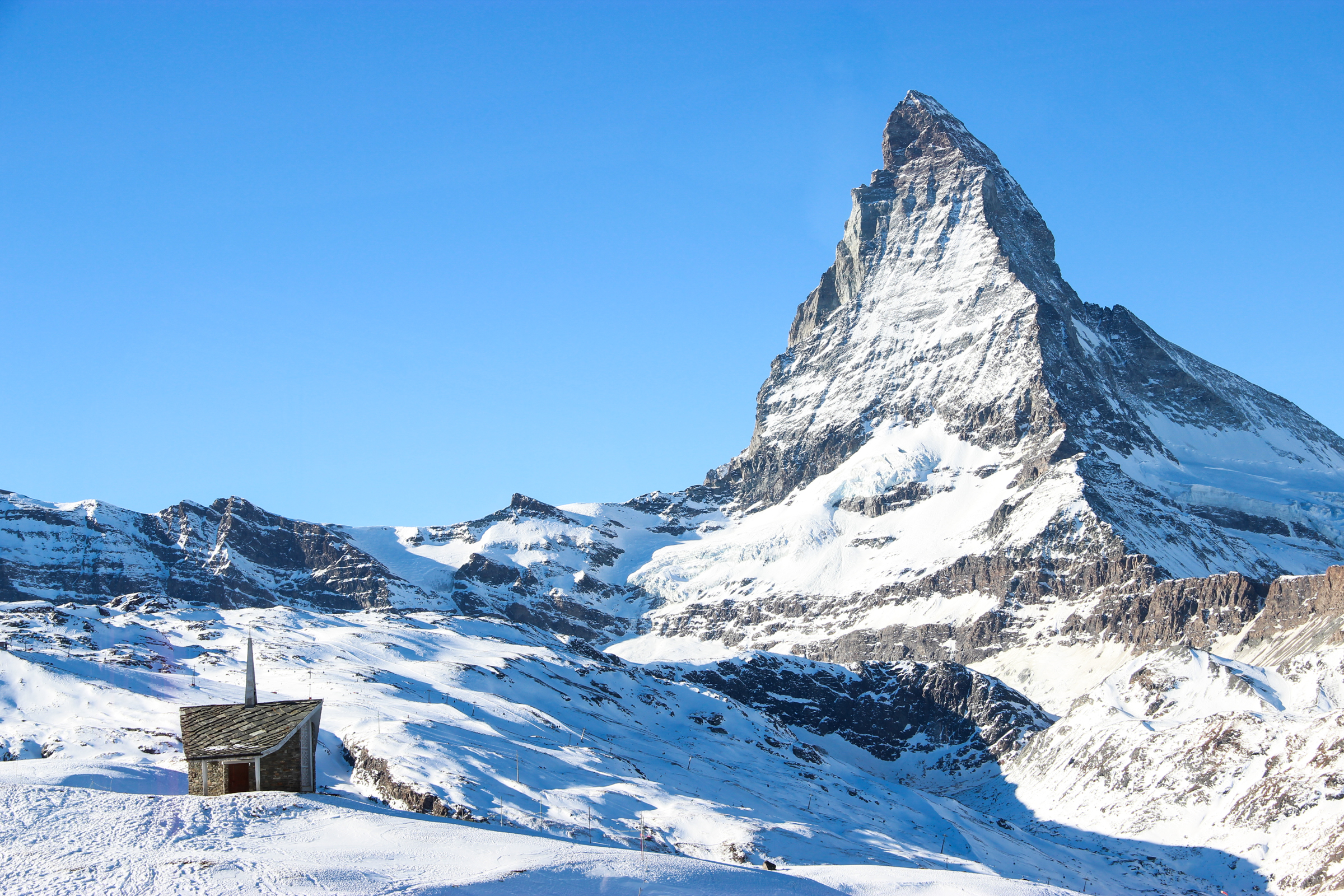 Free Stock Photo of Church by Snow Covered Mountain Peak