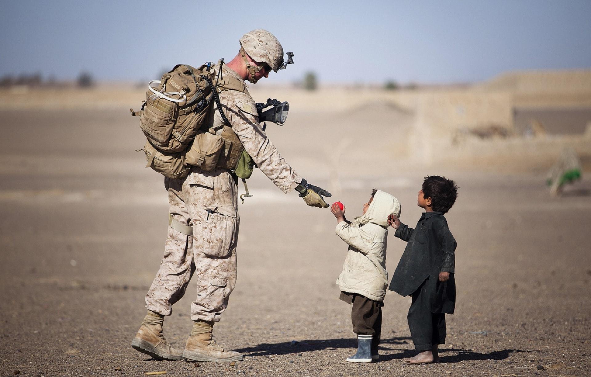 Soldier Giving Red Fruit on 2 Children during Daytime, Children, Desert, Friends, Help, HQ Photo