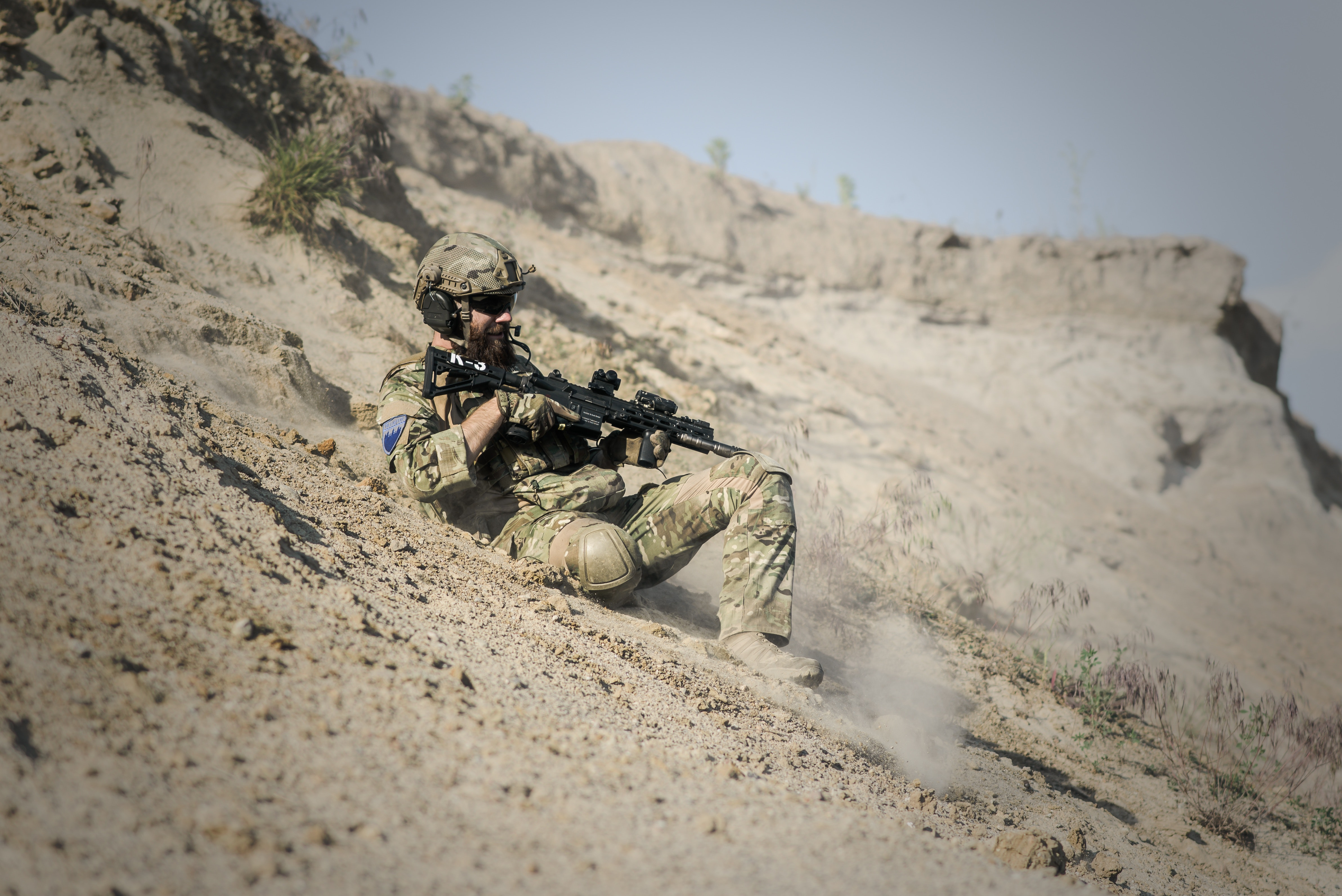 Soldier man with black rifle sliding on cliff photo