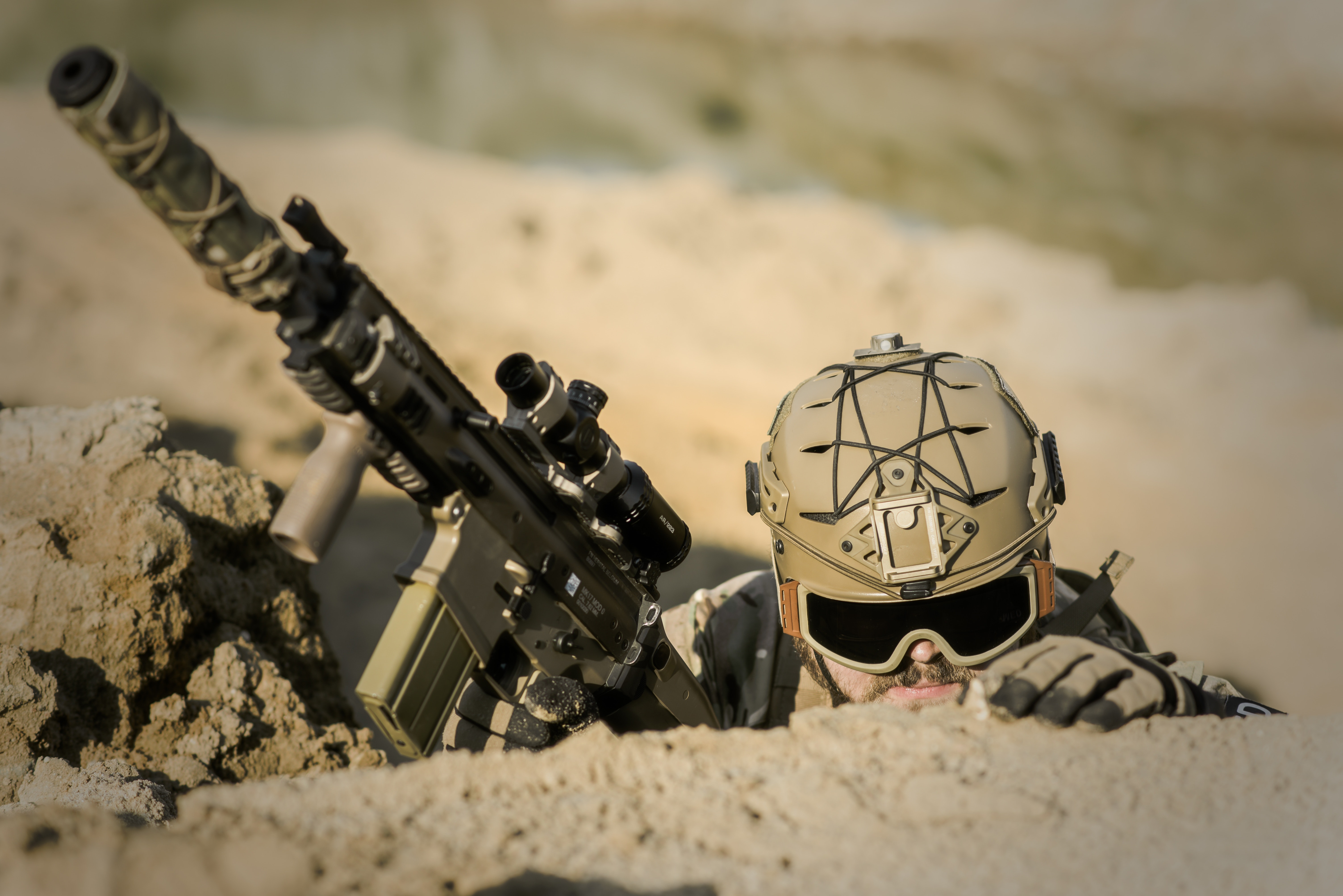 Soldier wearing brown helmet holding assault rifle during daytime photo