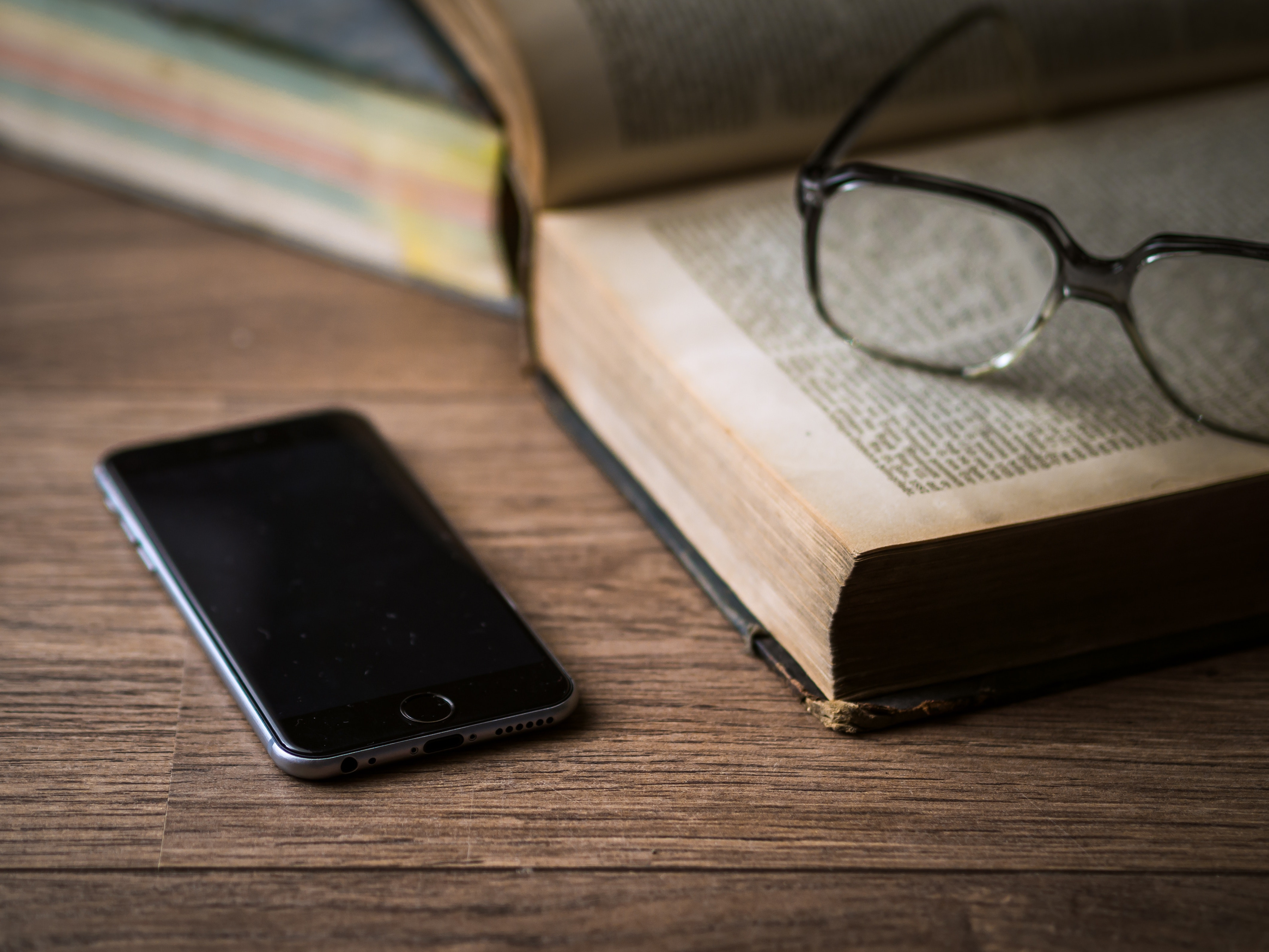 Space gray iphone 6 on top of brown table beside book photo
