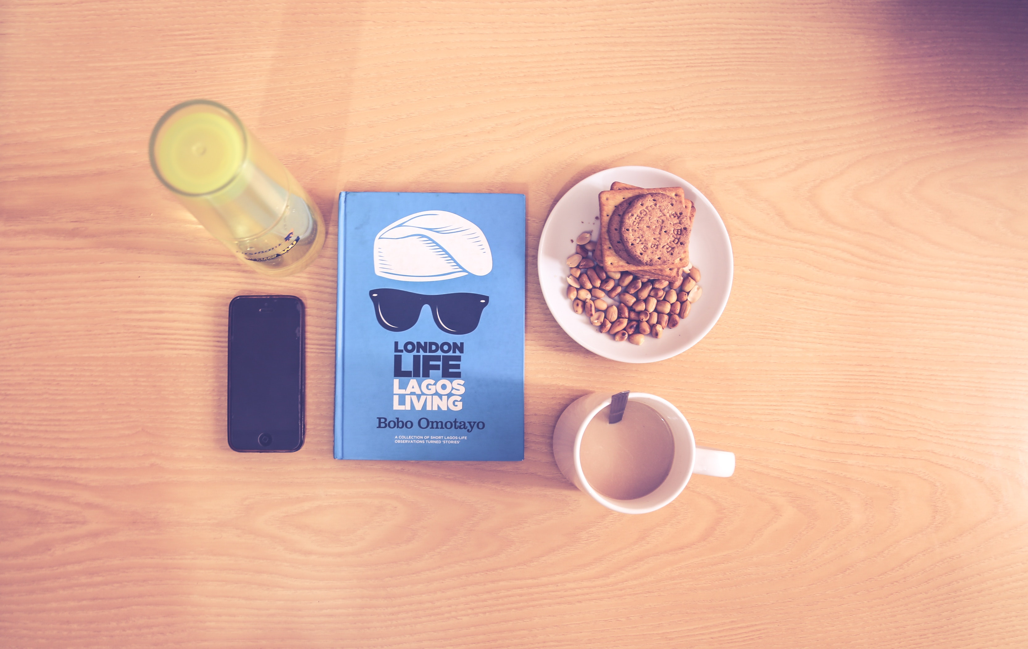 Space gray iphone beside blue labeled book near white ceramic cup with liquid content photo