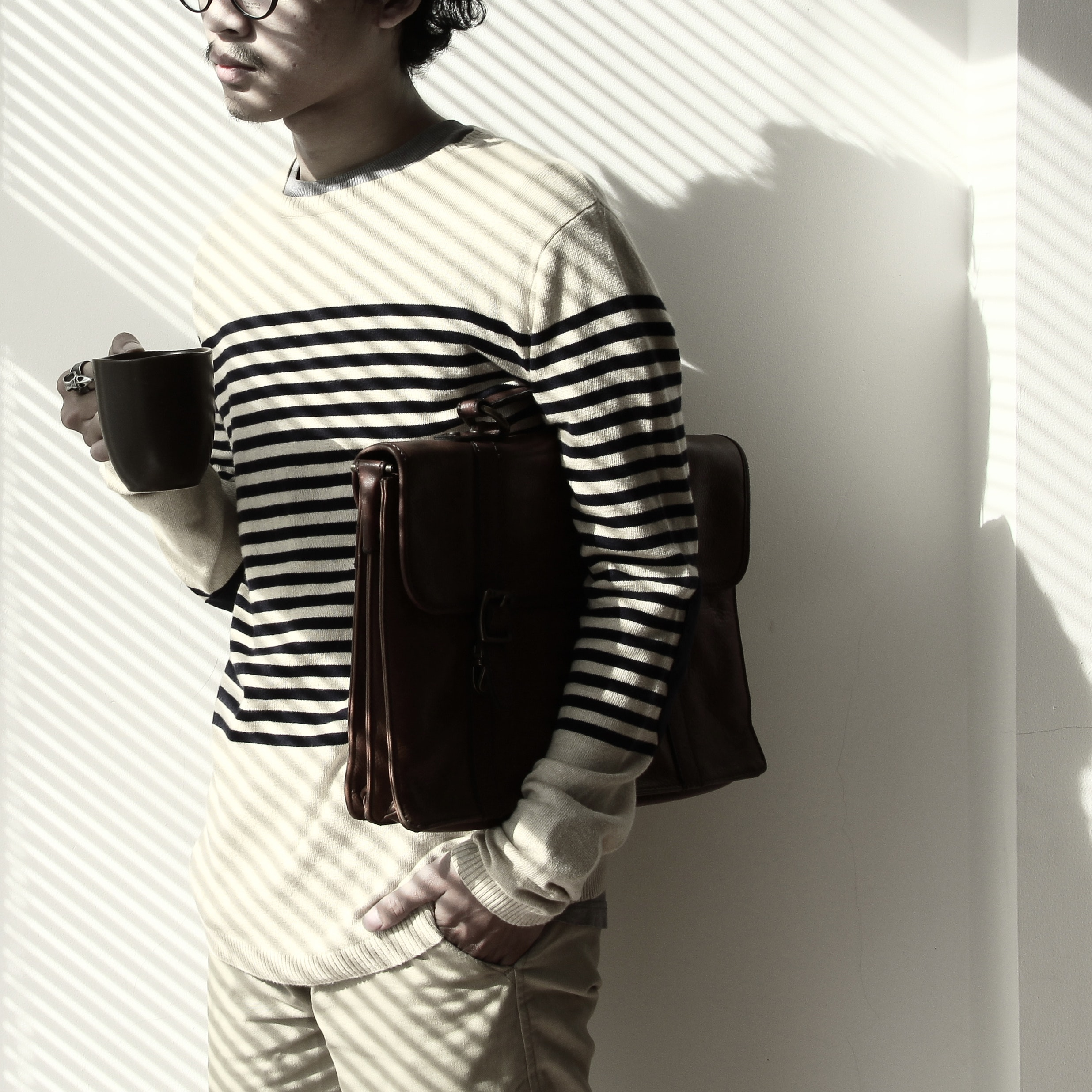 Standing brunet person waring eyeglasses and white black stripe sweater holding mug and briefcase photo