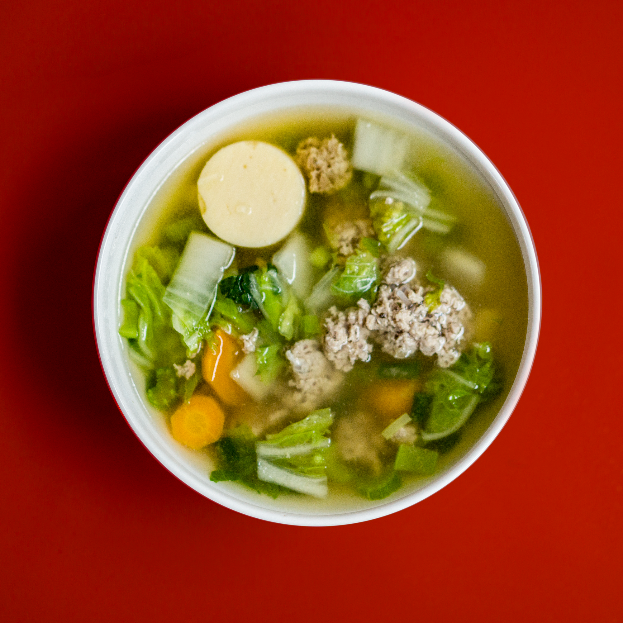 Stew with meat and vegetables placed in white ceramic bowl photo