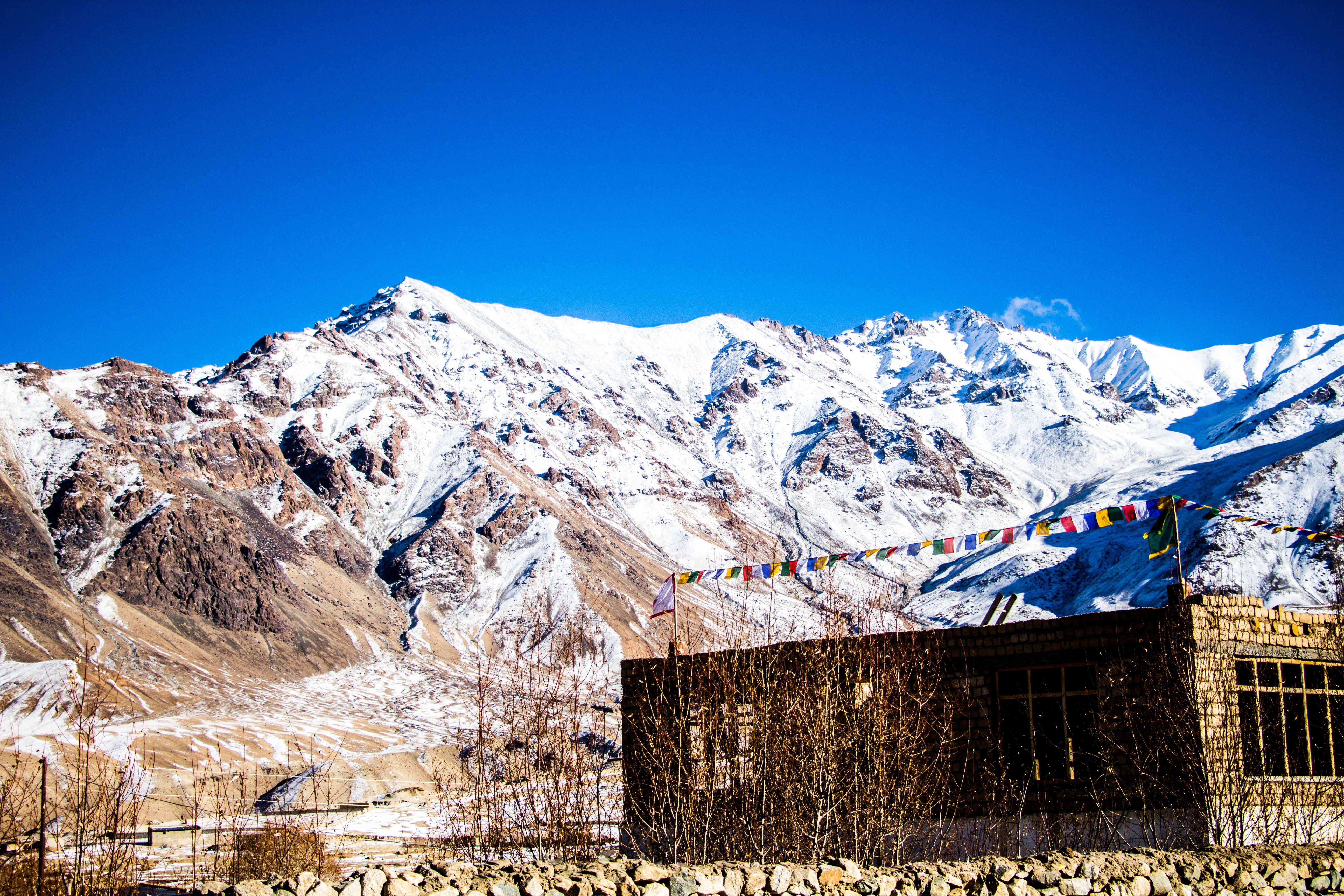 Stone building at the base of snow-covered mountain range under clear bright blue sky photo