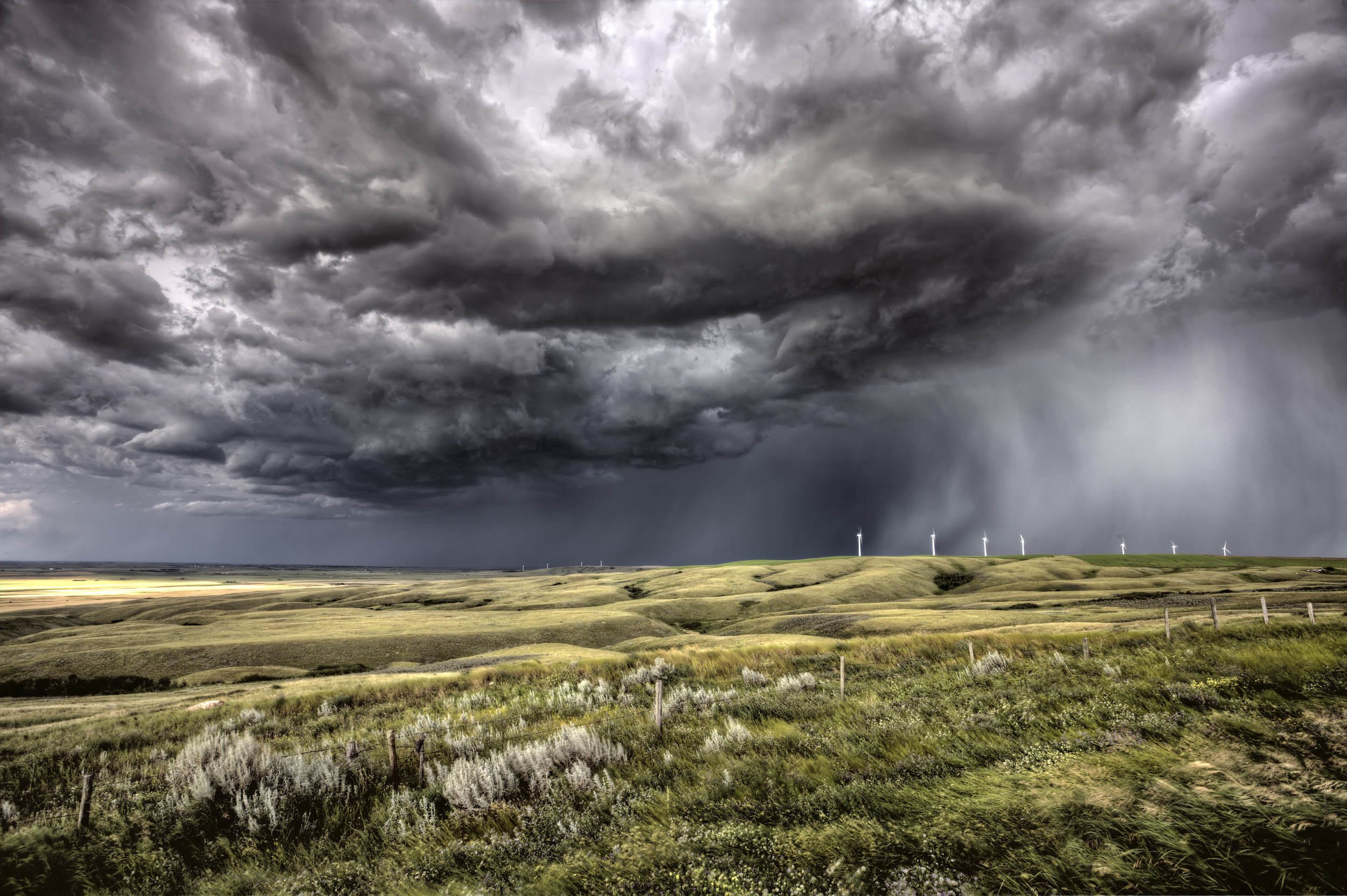 Storm clouds forming over a wind farm • Earth.com