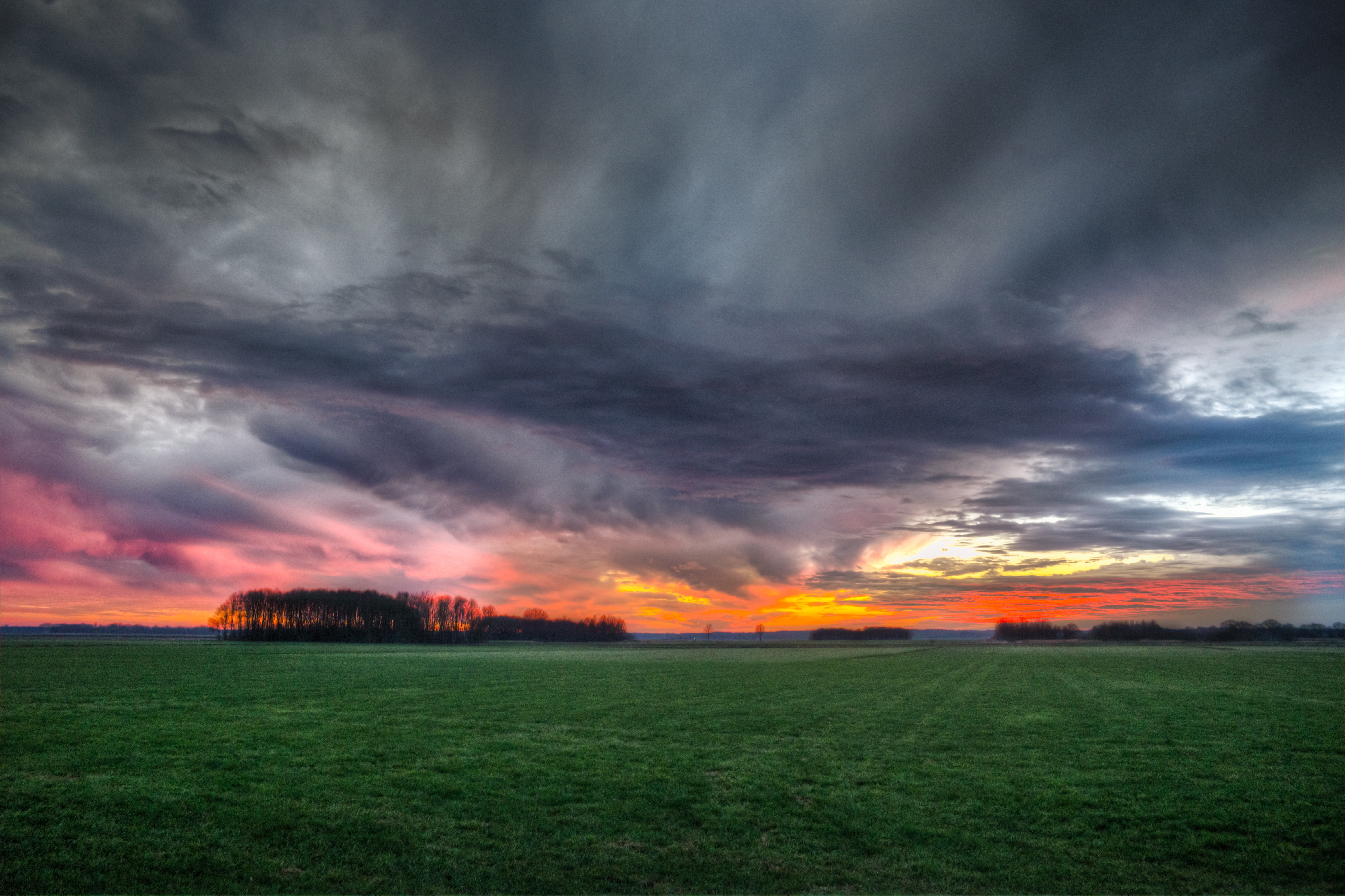 Storm clouds over field during sunset photo