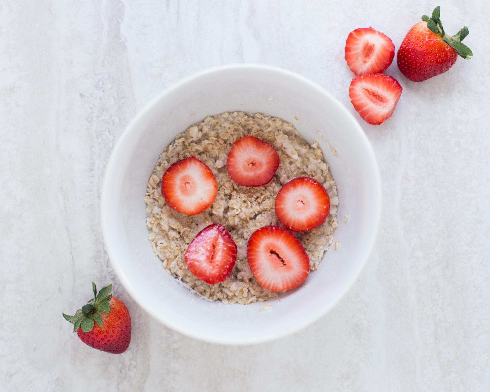 Strawberry on table top near white ceramic bowl photo