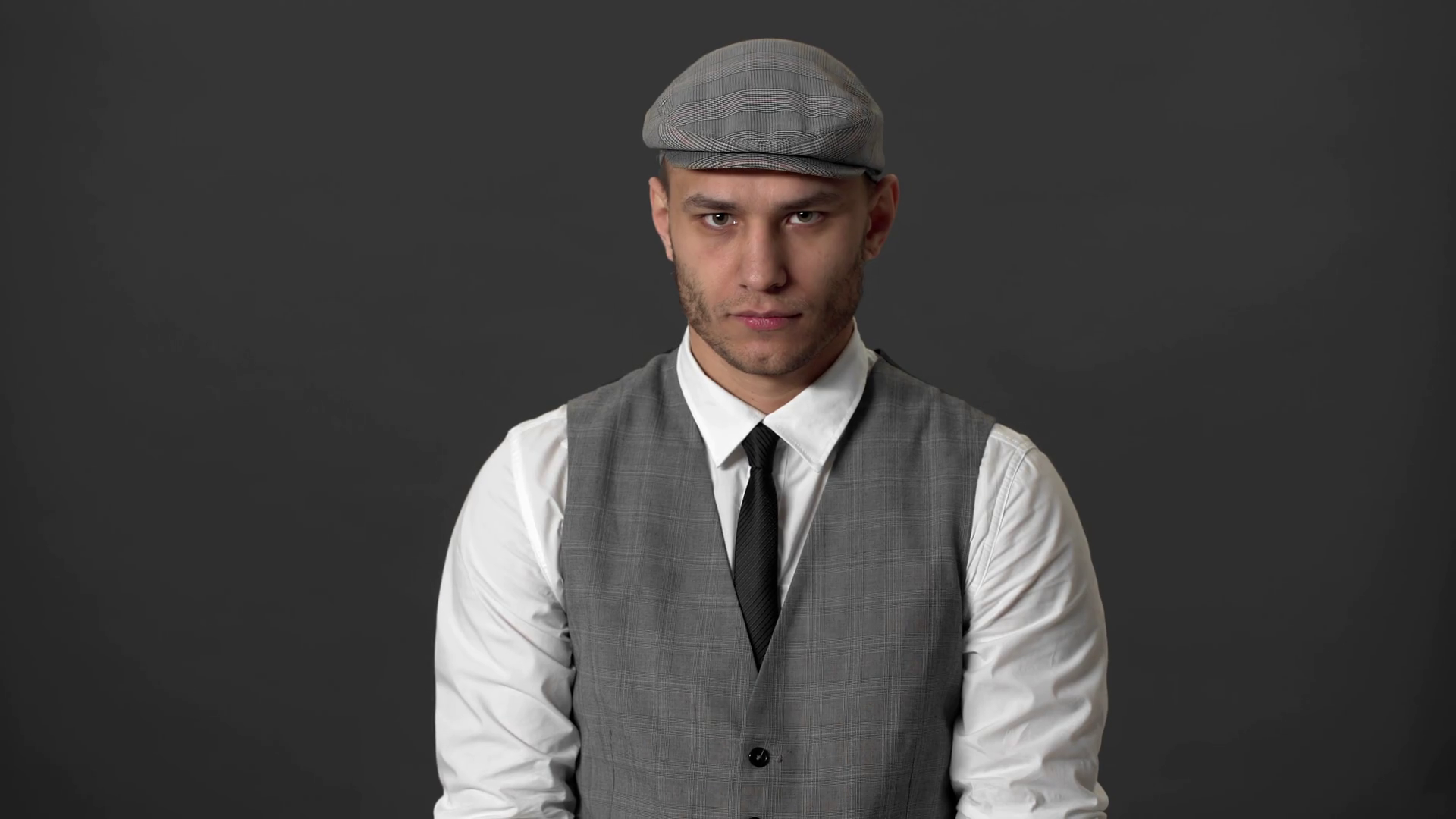 Portrait of stylish guy wearing suit and flat cap posing on camera ...