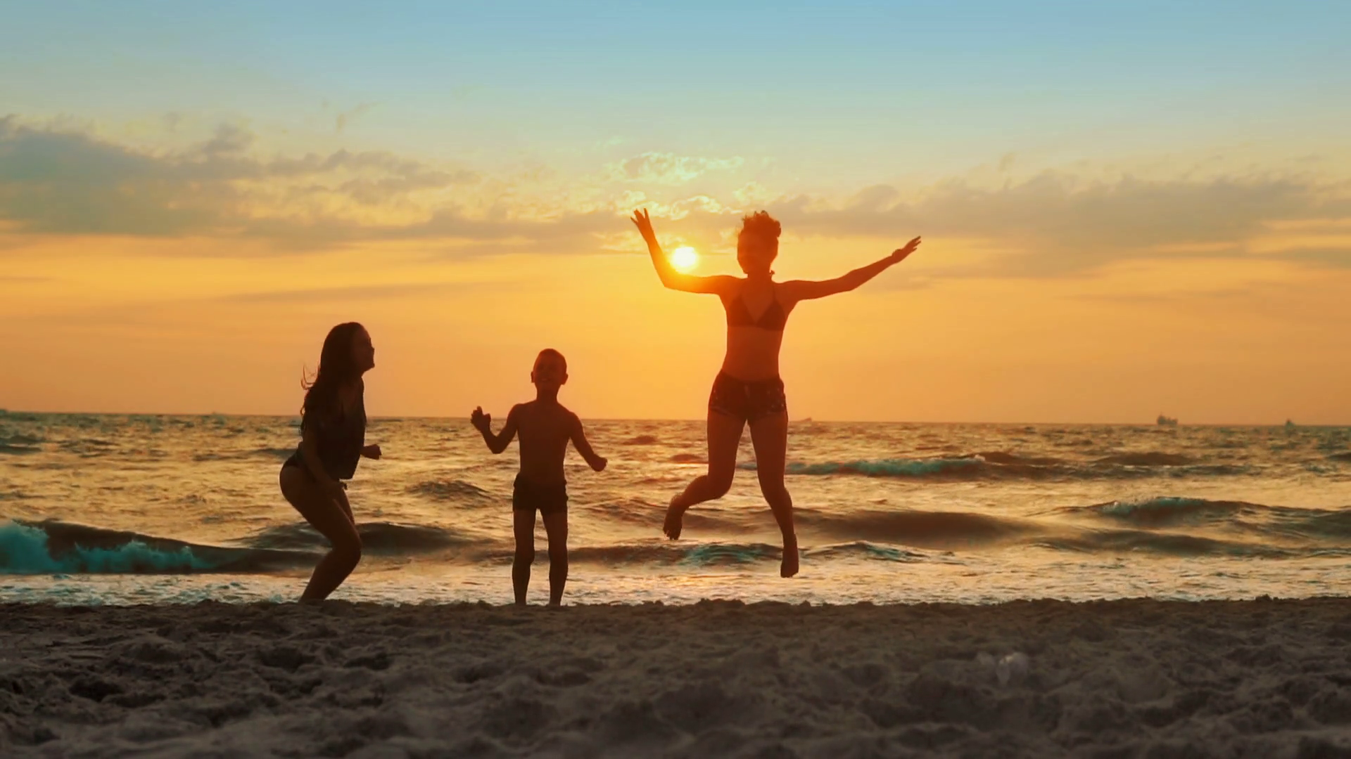 Group of kids having fun jumping on the beach at sunset SLOW MOTION ...