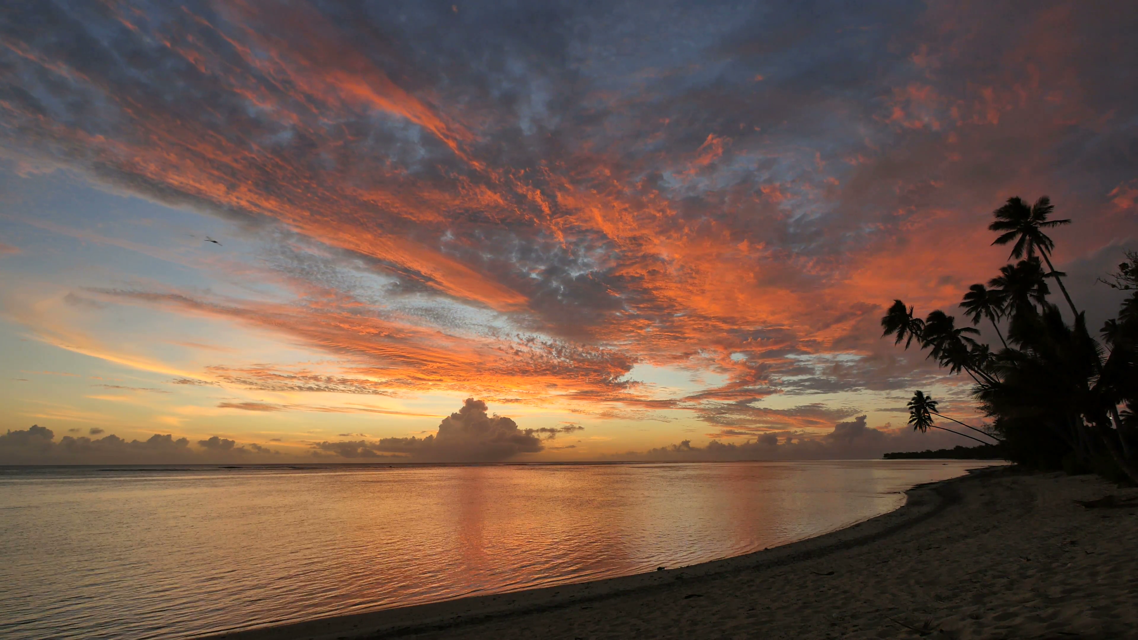 Static very wide shot of a beach at sunset in Rarotonga, Cook ...