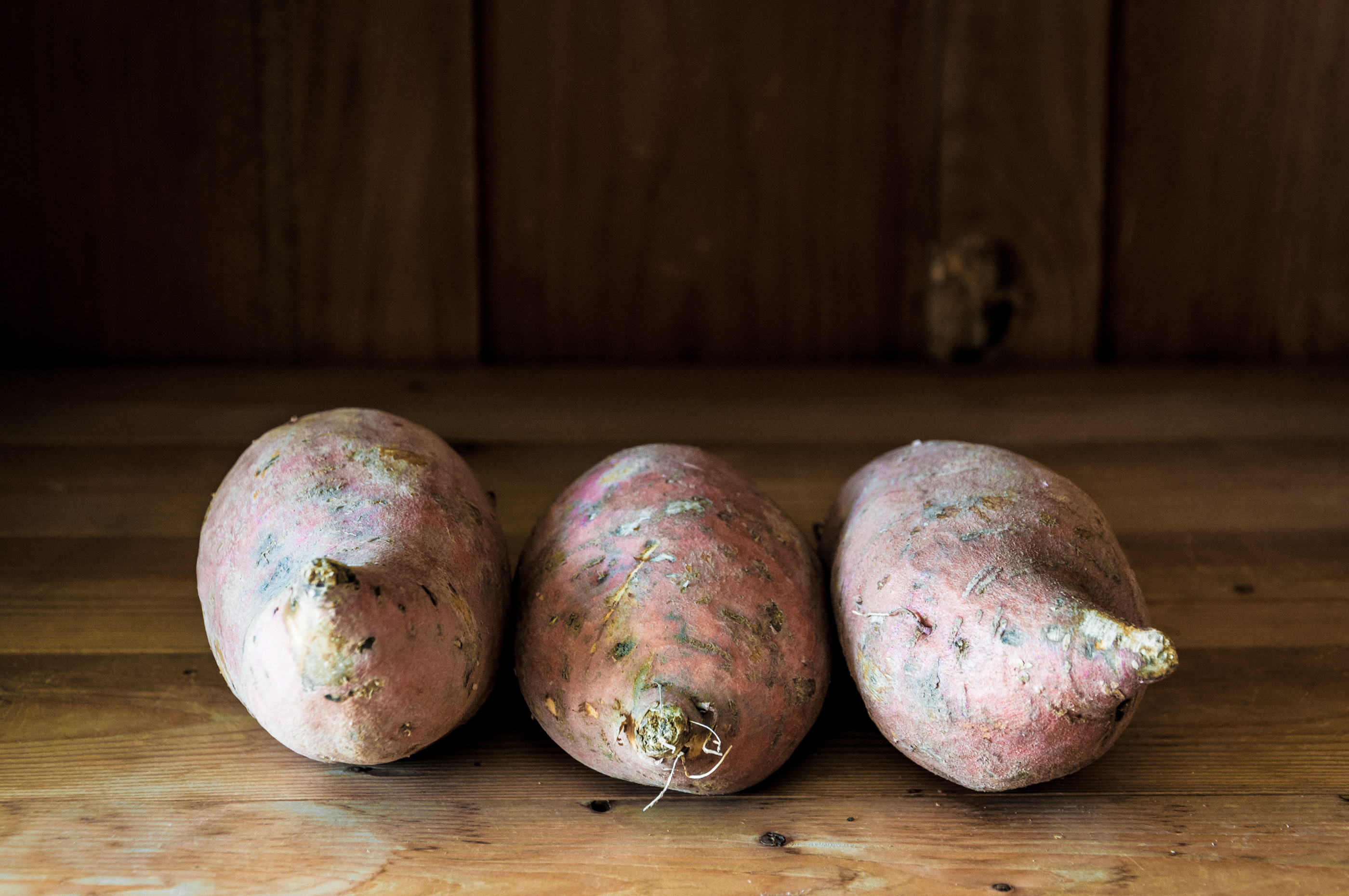 Sweet potatoes on wooden background photo