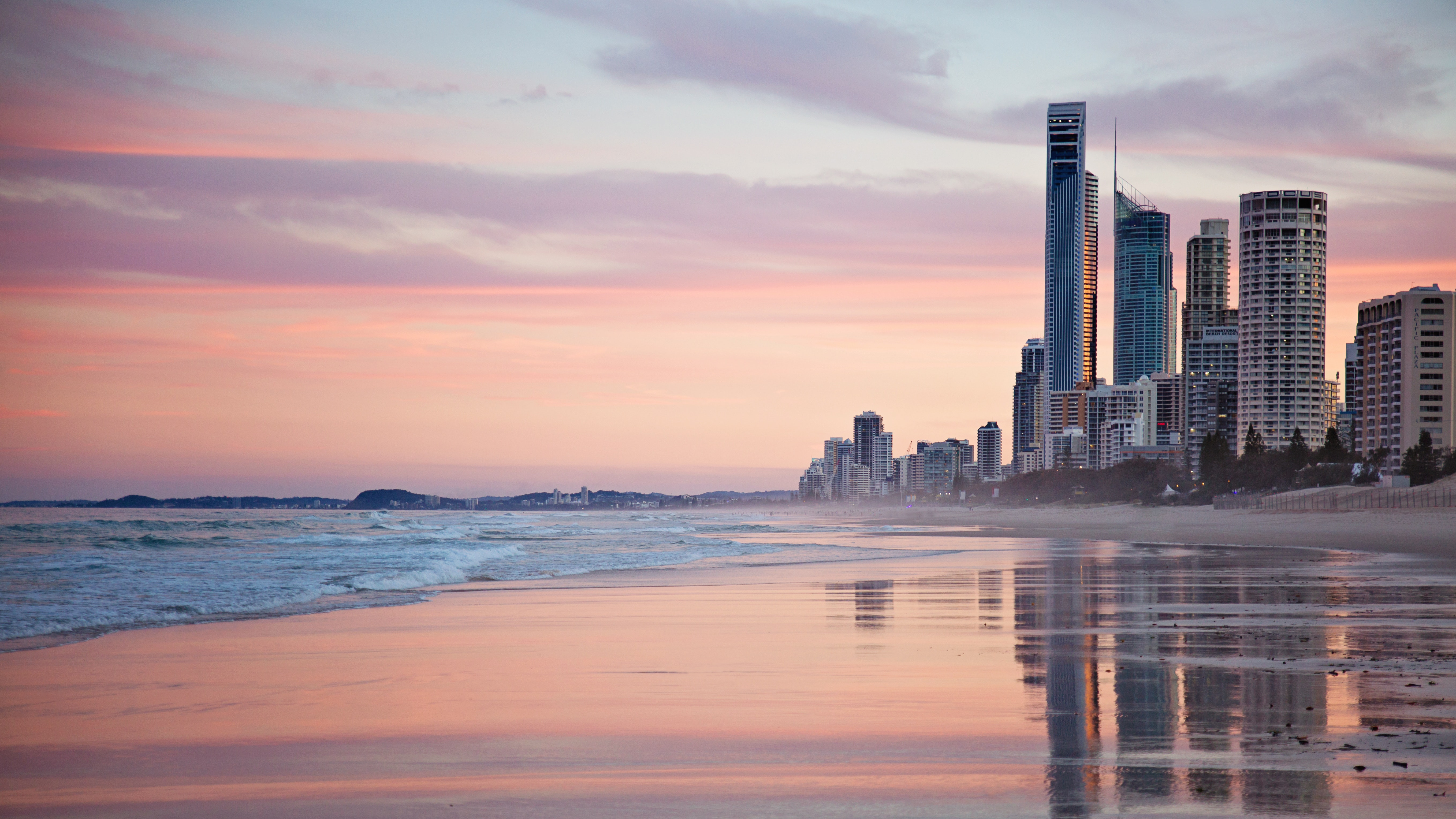 Tall city buildings near beach shore during sunset photo