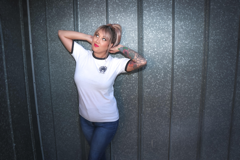 Tattooed woman wearing white shirt and denim pants photo