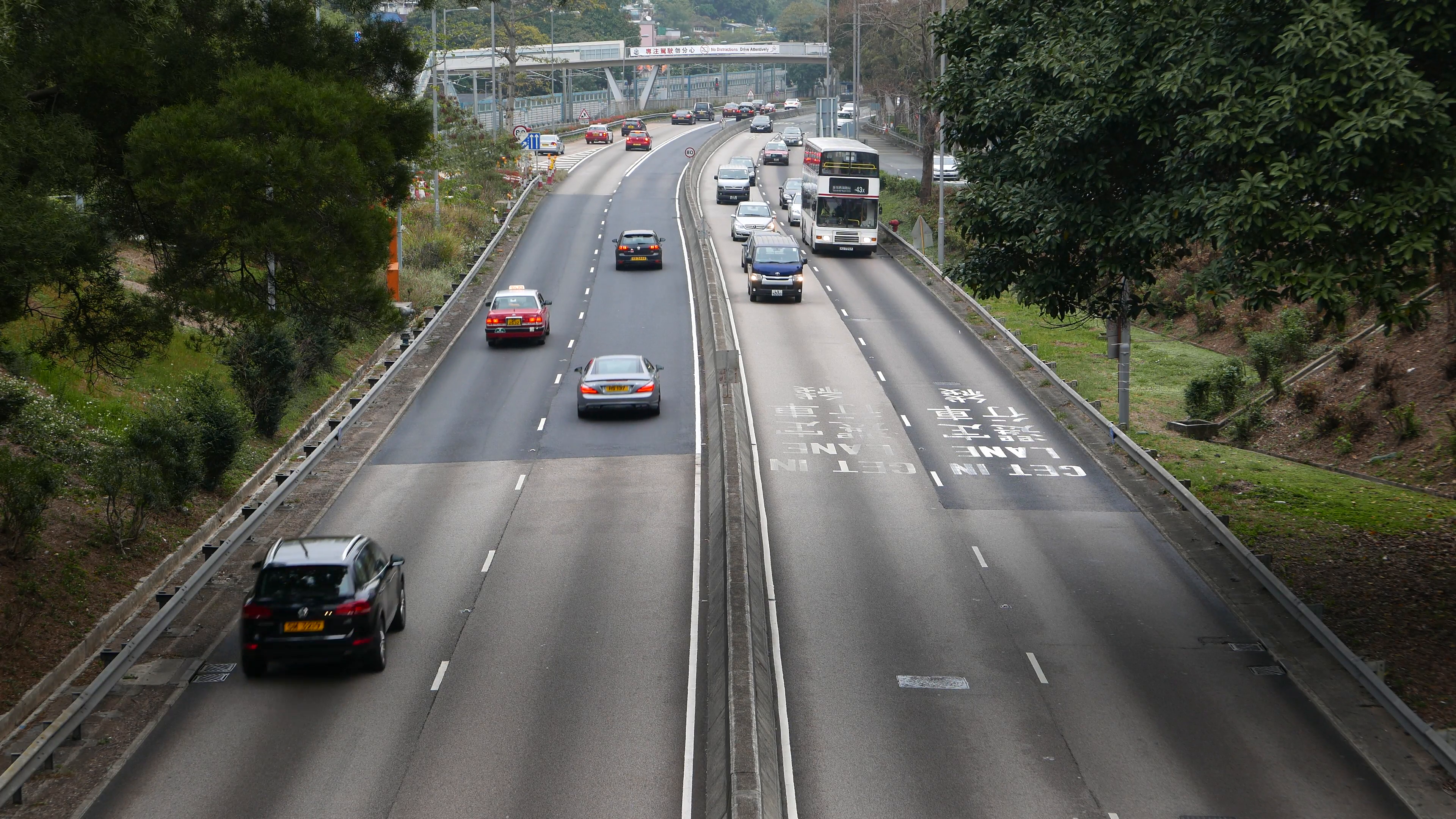 Left-hand drive road and traffic, car overtake bus, change lane ...