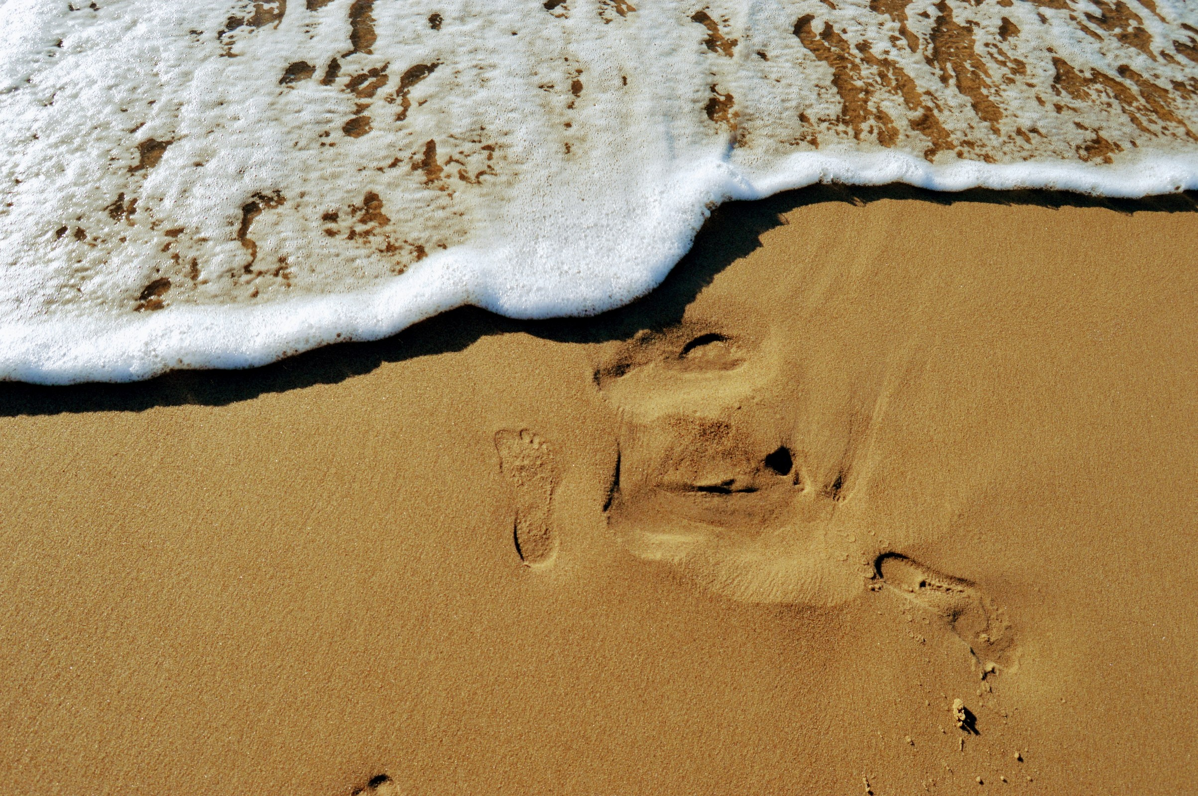 The imprint of a bare foot on the sand photo