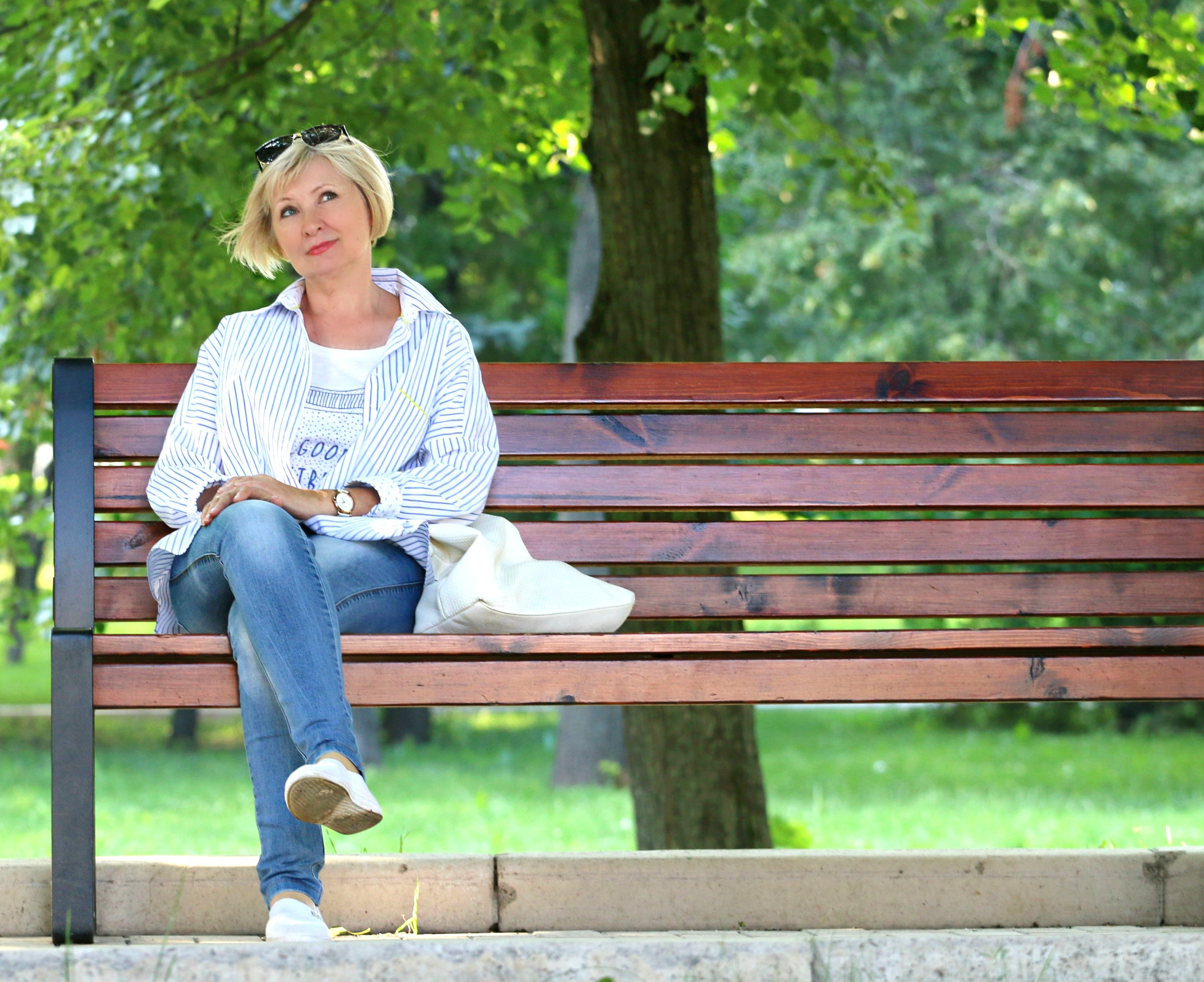 Thinking woman in white jacket and white scoop neck shirt blue denim jeans sitting on brown wooden bench beside green trees during daytime photo