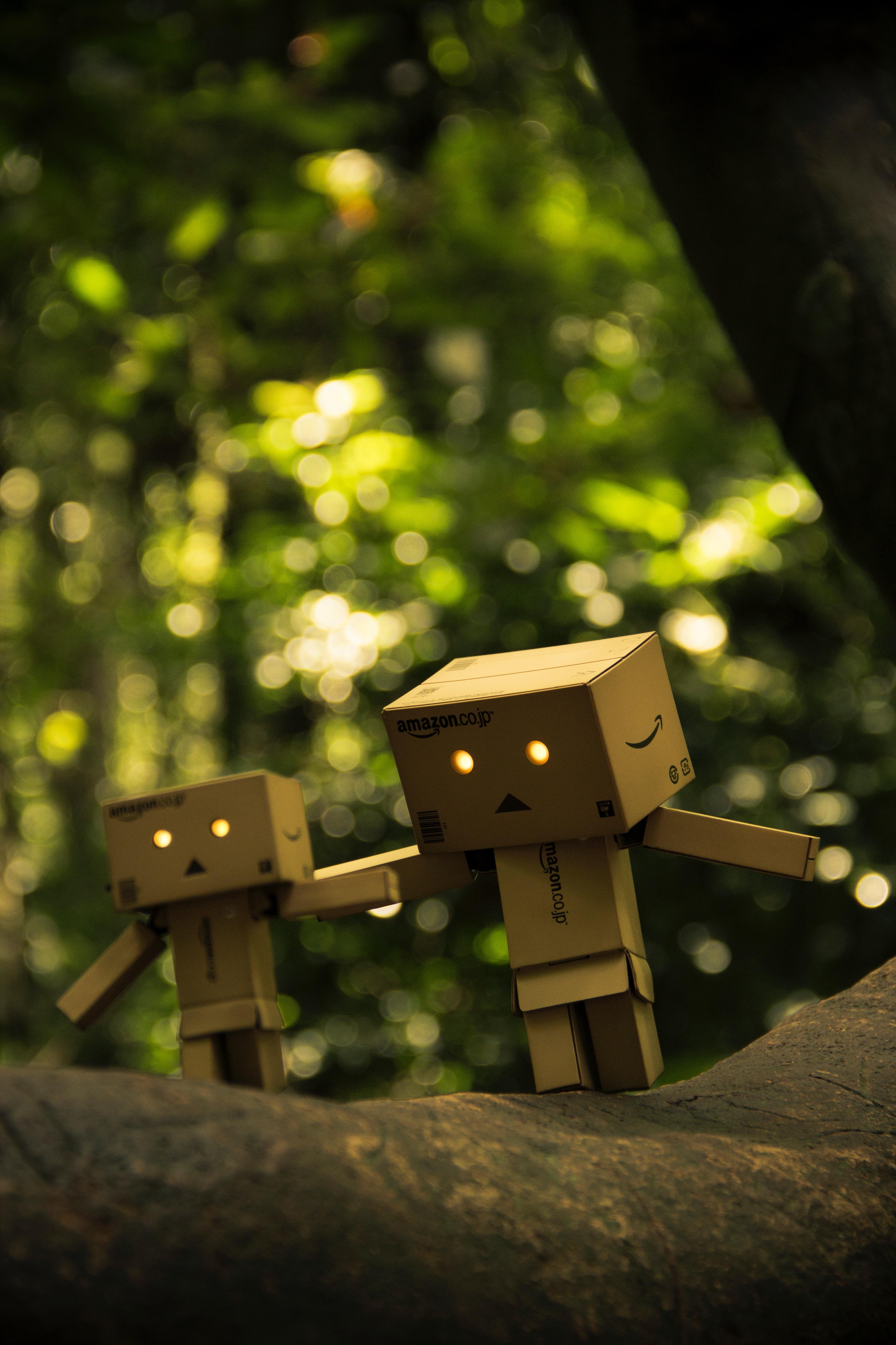 Three brown cardboard box figures on brown surface photo