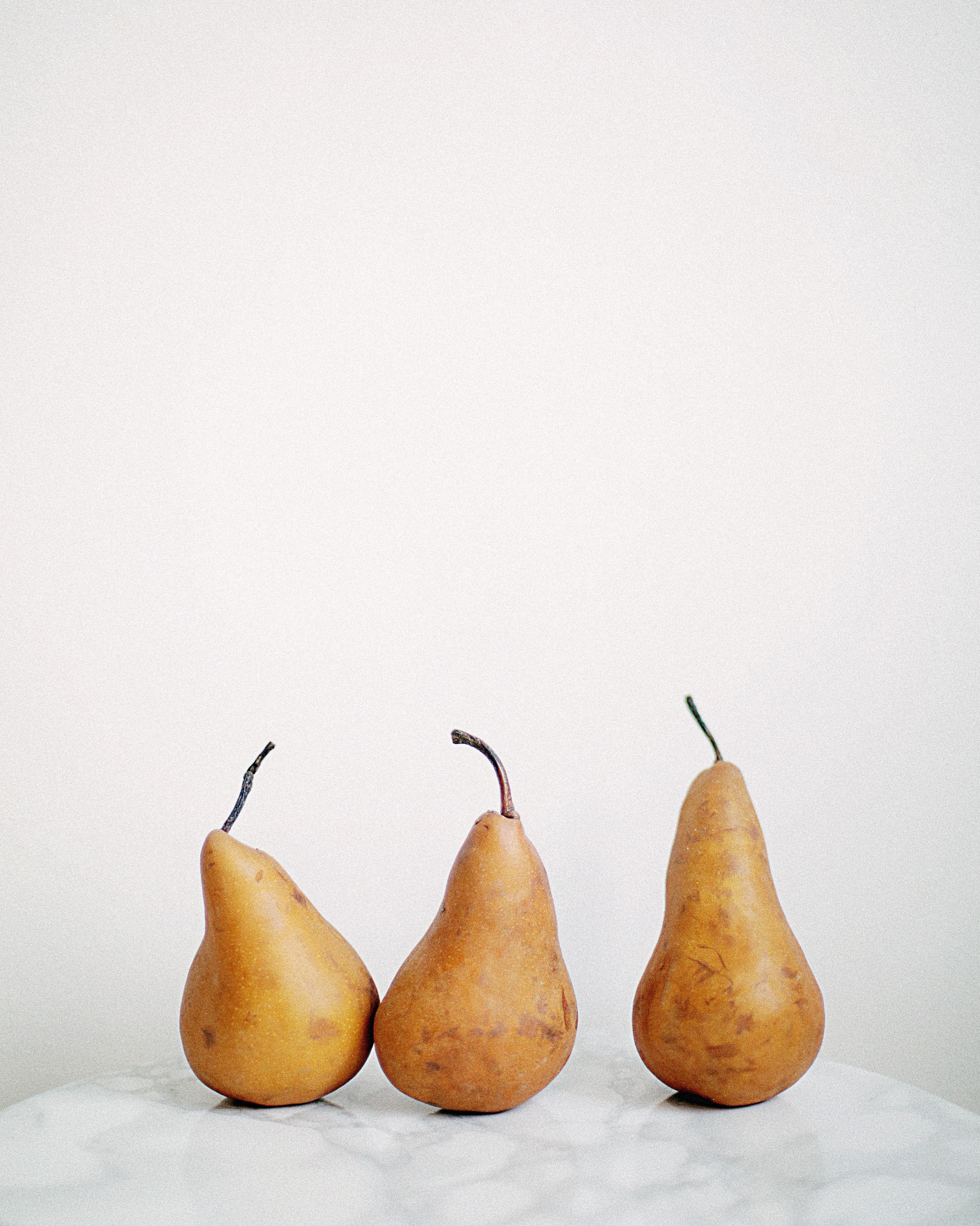 Three brown fruits on white textile photo