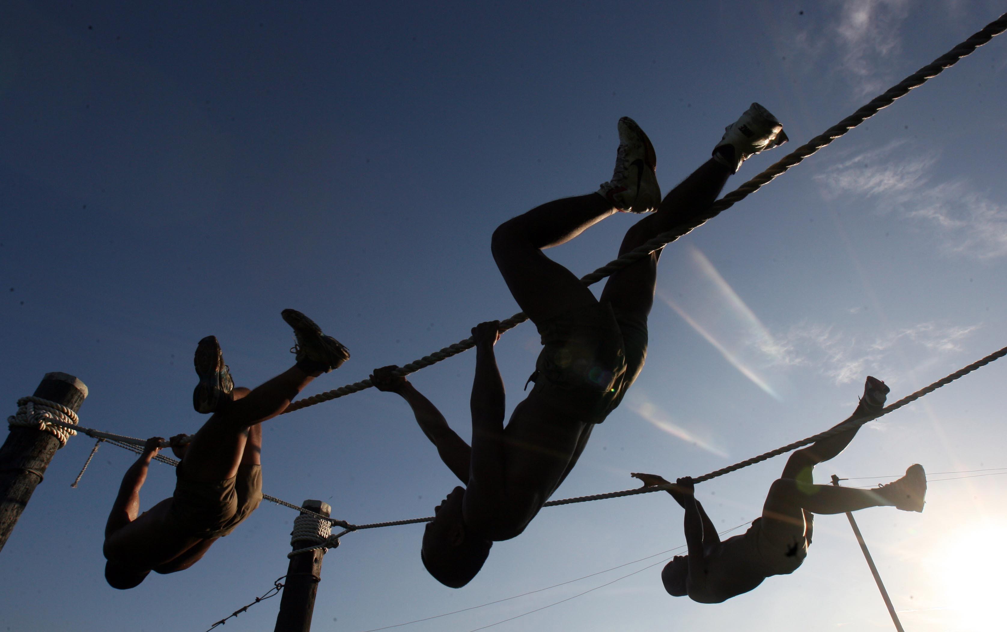 Three man climbing on rope under the sunset photo