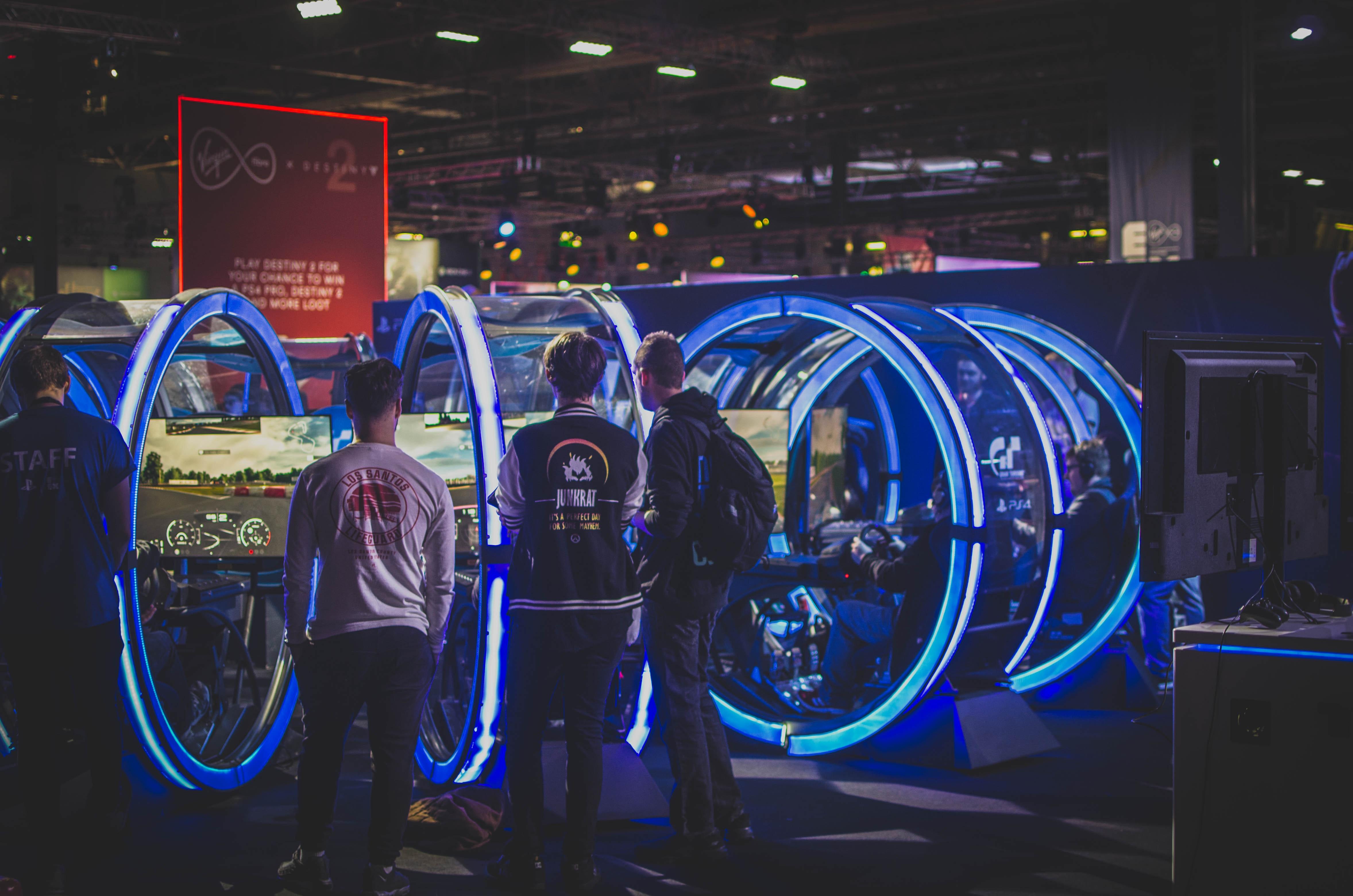 Three men standing in front of racing arcade machines photo
