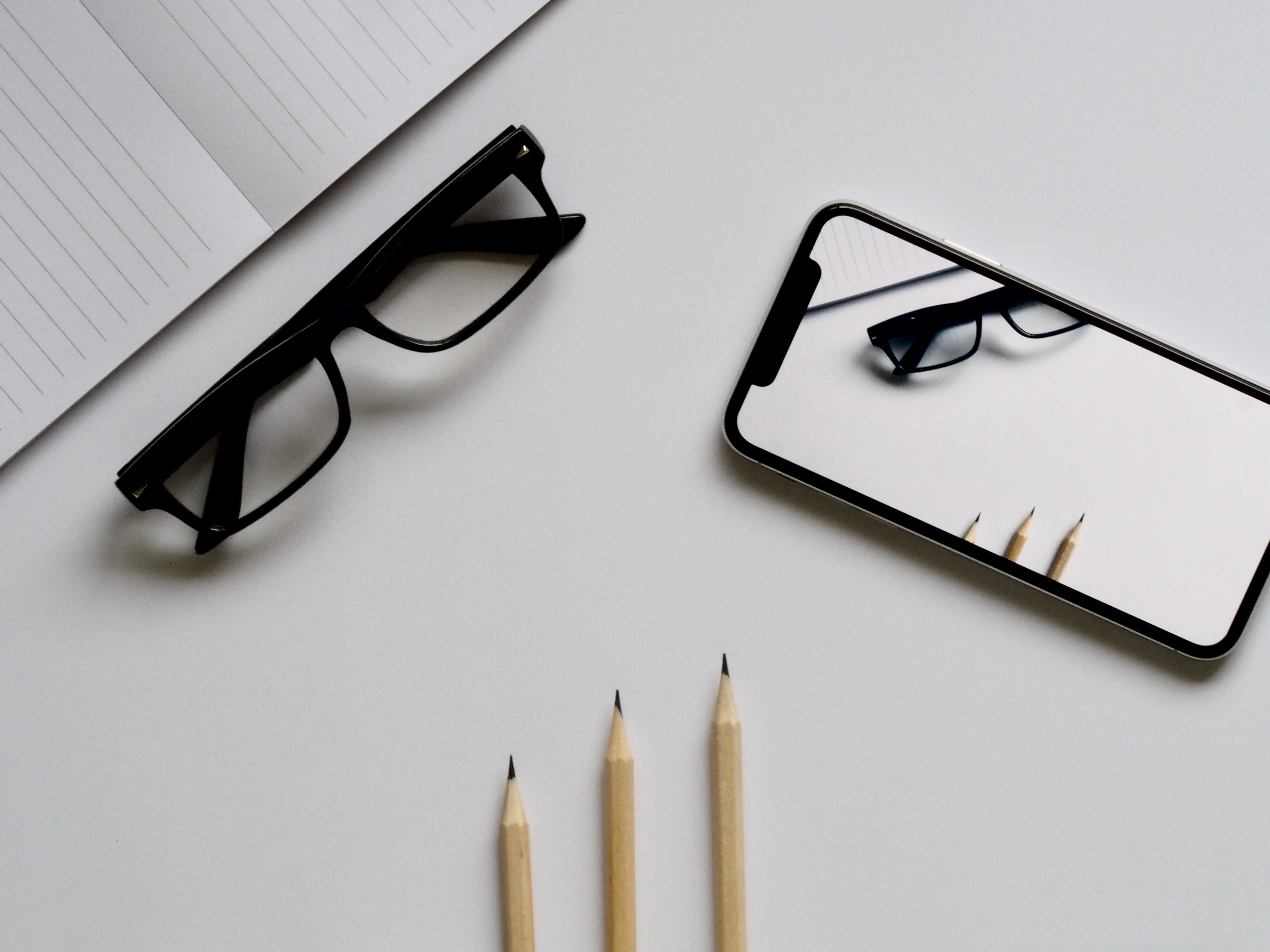 Three pencils, eyeglasses, and smartphone on white table photo