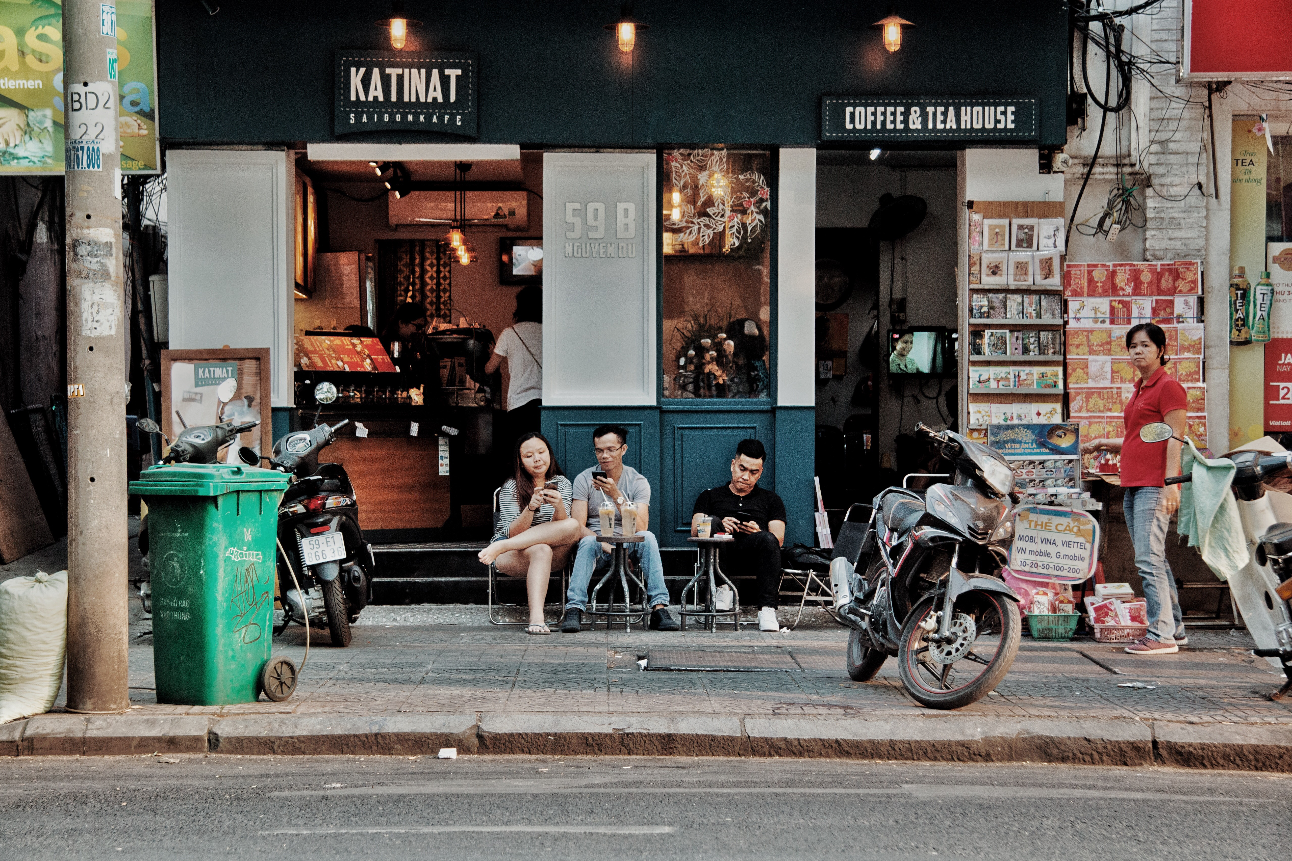 Three people sitting on chairs outside coffee & tea house near motorcycles photo