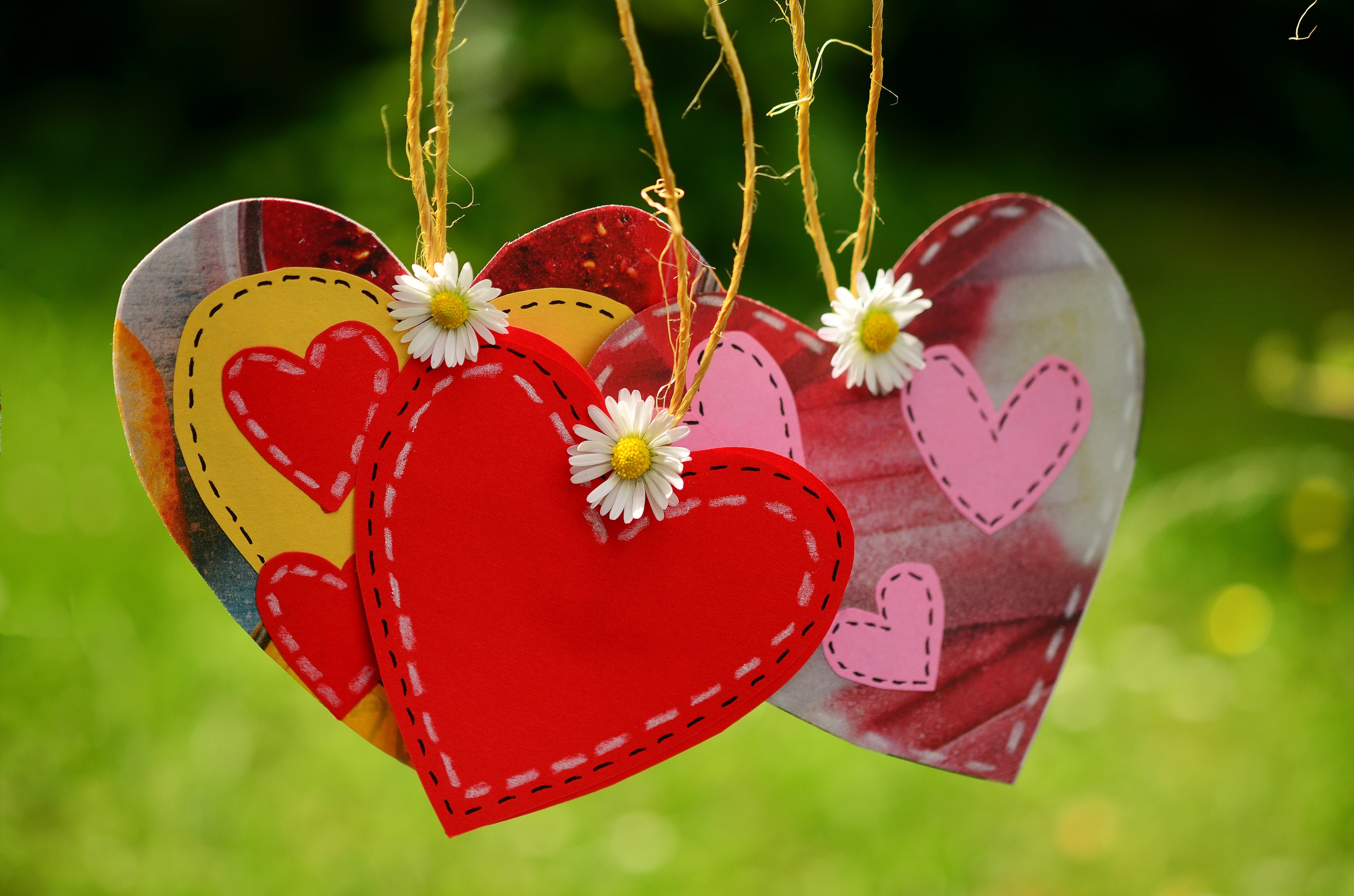 Three red hearts hanging with white flowers photo