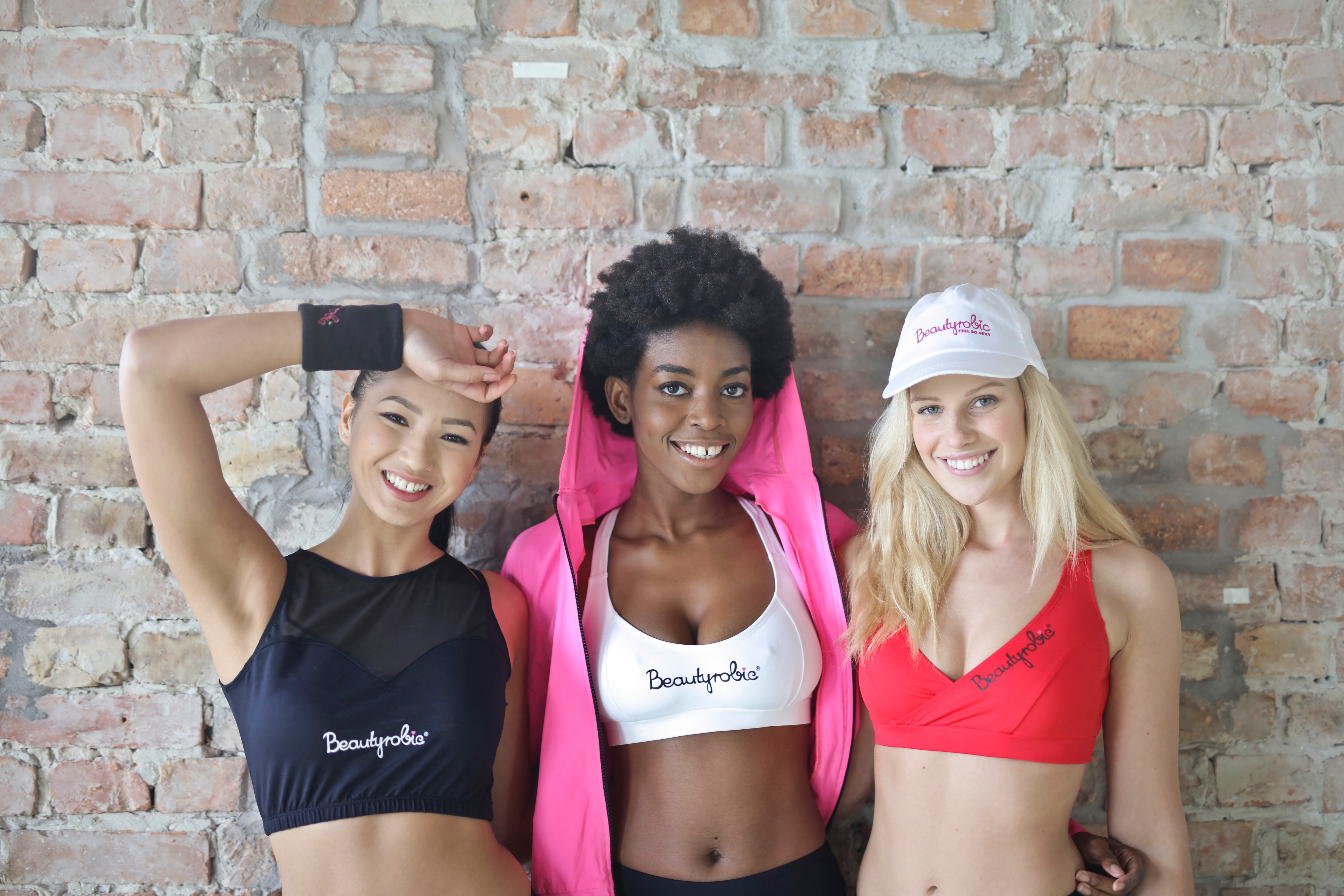 Three women wearing sport bra standing behind concrete wall photo