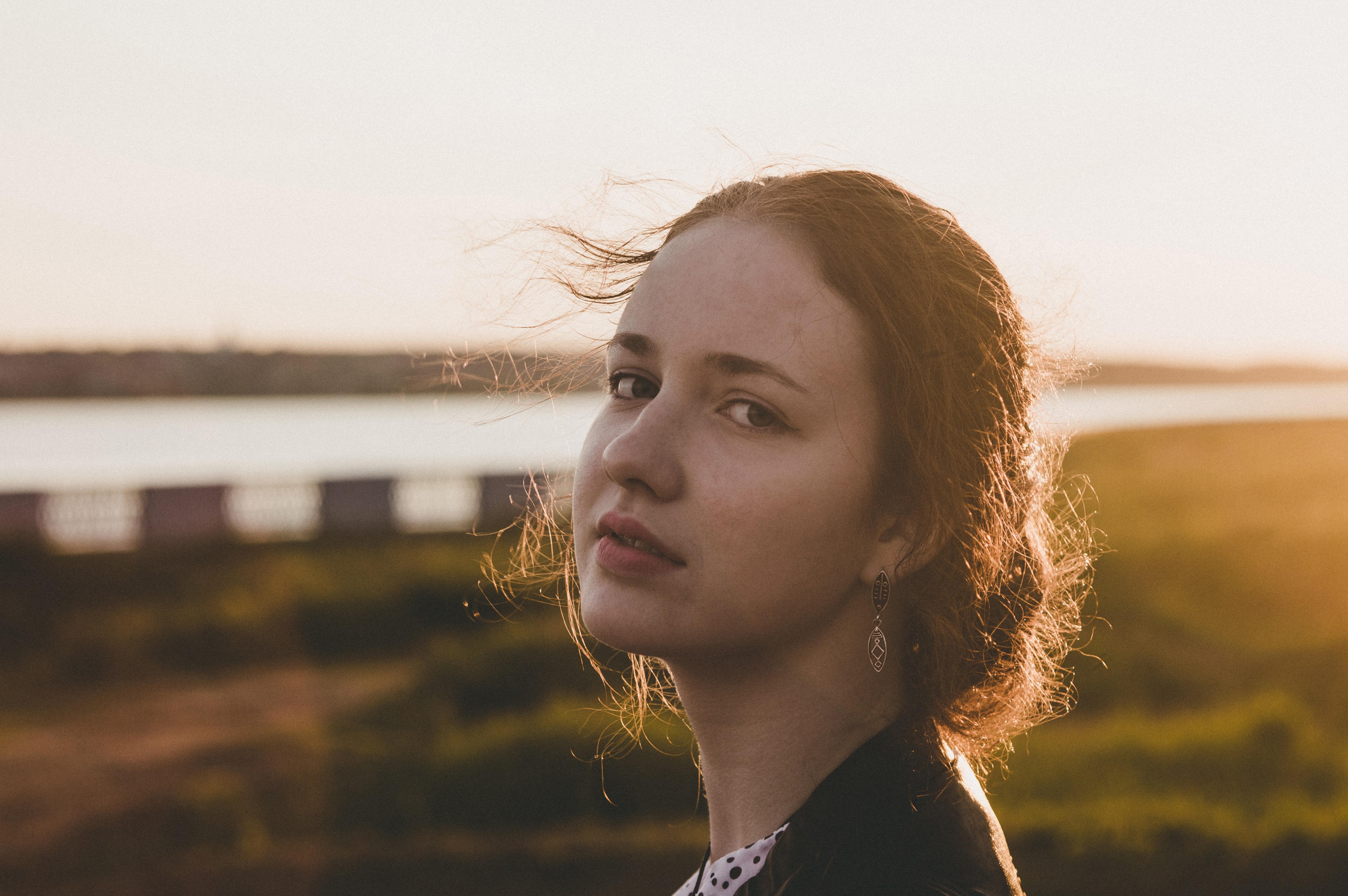 Tilt shift lens photography of woman during sunset