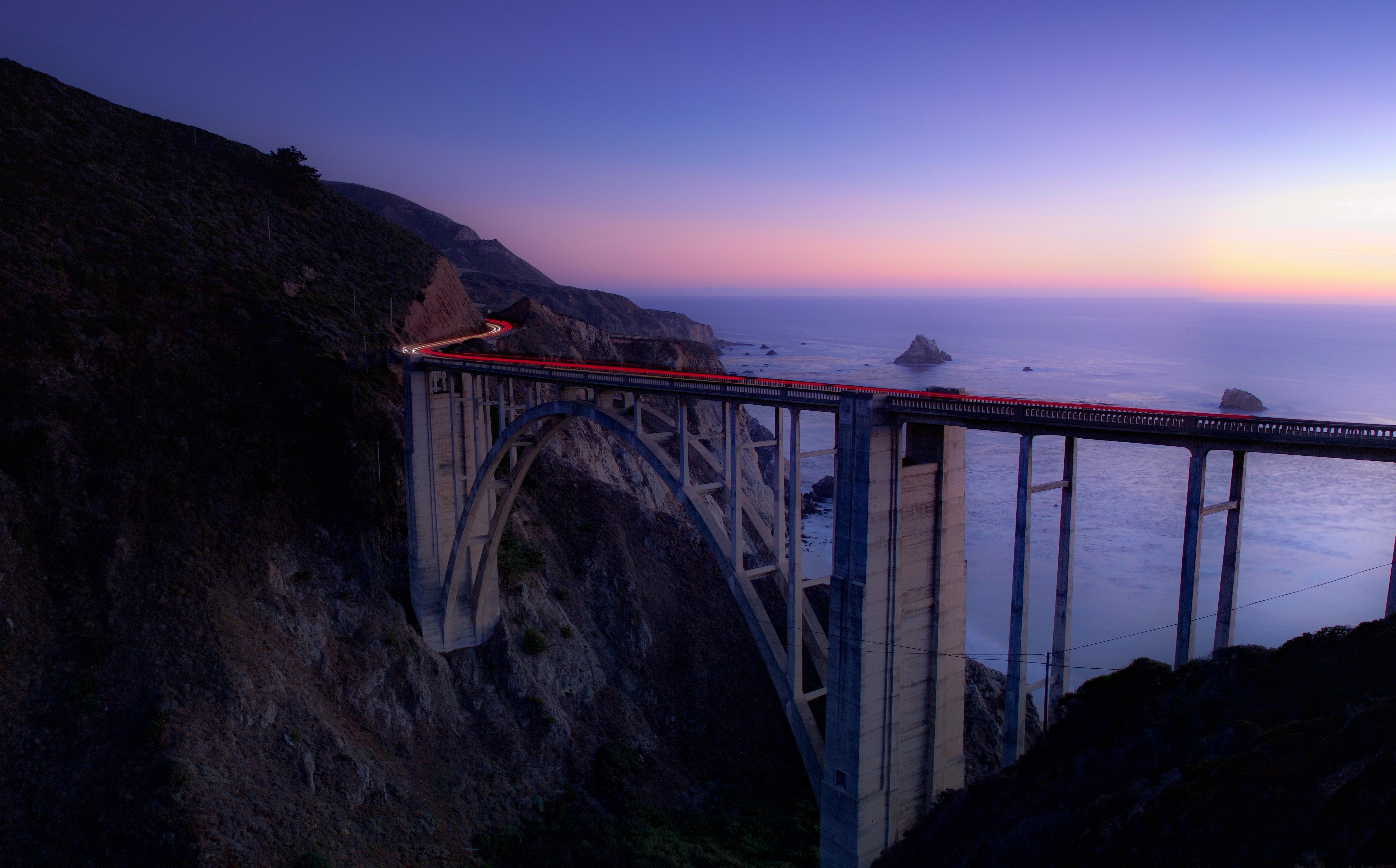 Time lapse photography of cars running on bridge near ocean