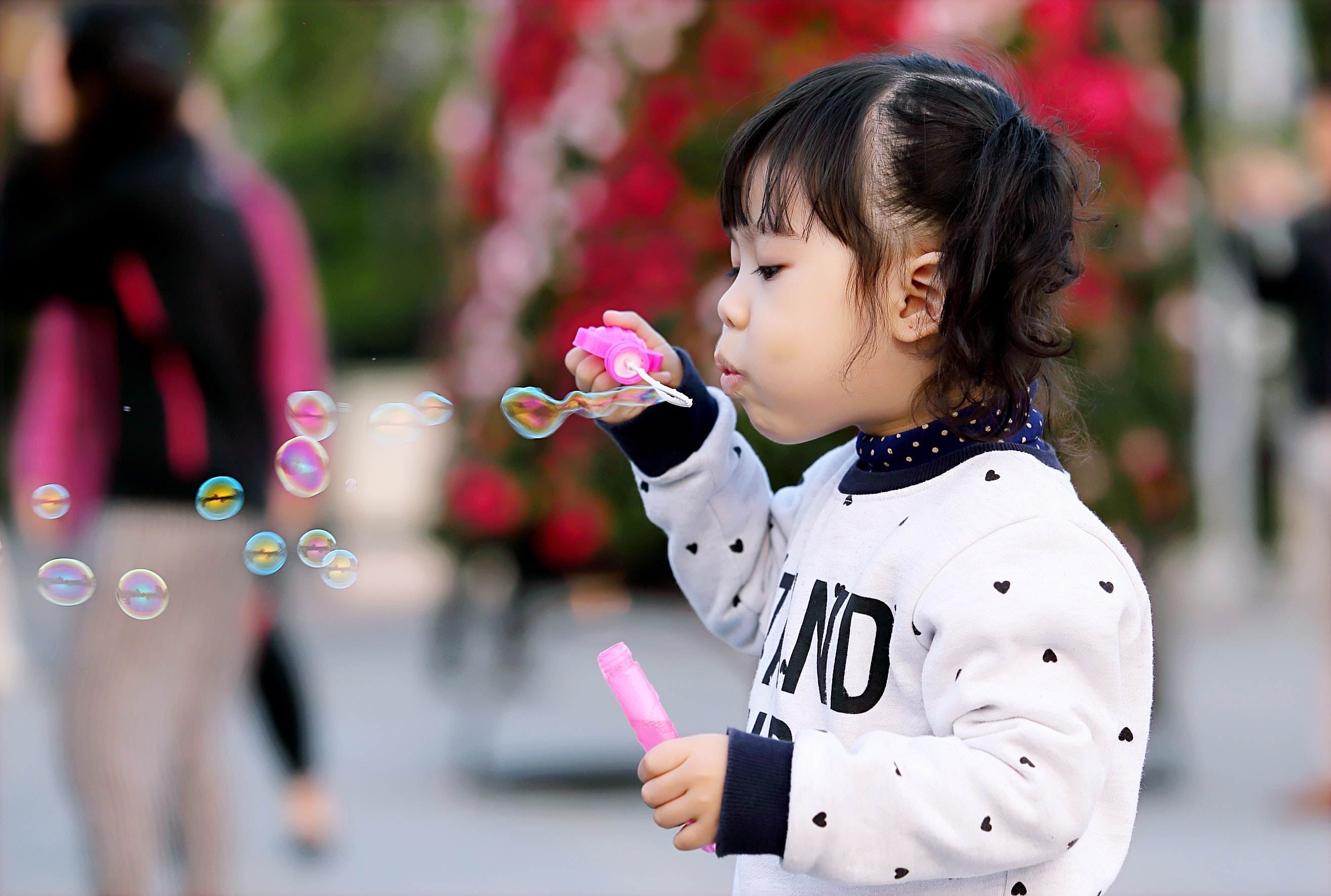 Toddler girl wearing white and black sweater holding plastic bottle of bubbles at daytime photo