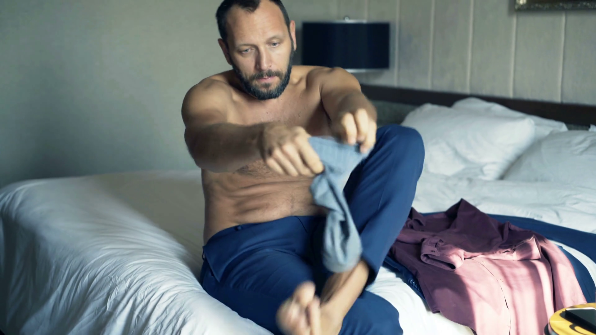 Young businessman putting on socks sitting on bed at home Stock ...