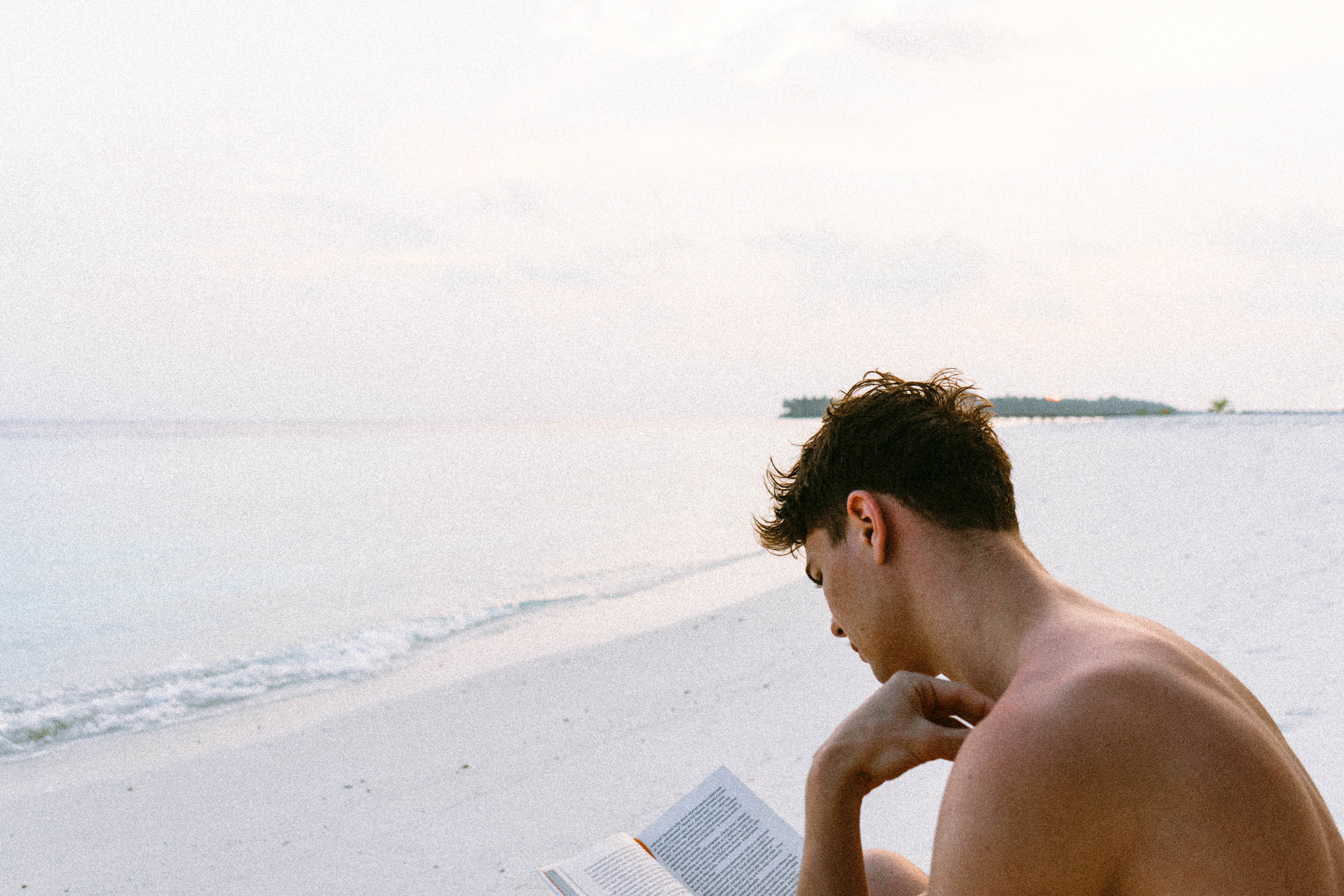Topless man reading book while seating at beach photo