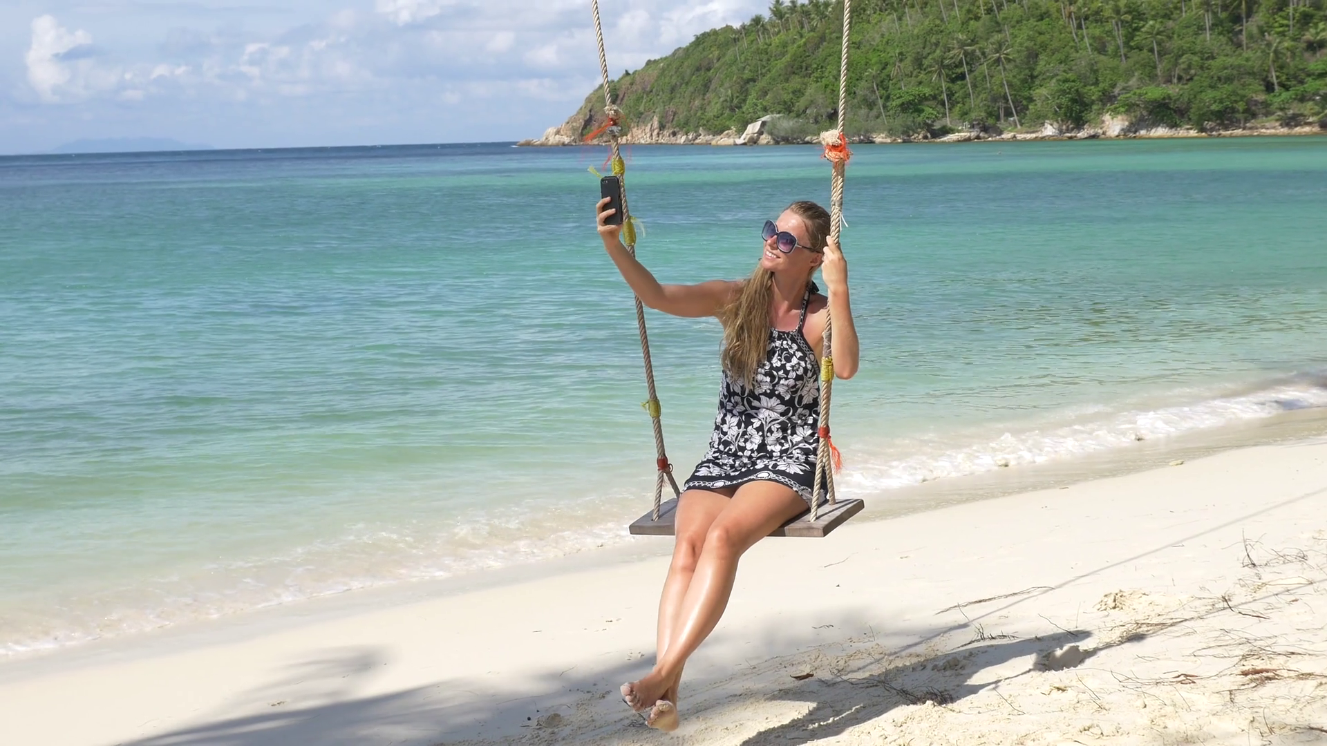 Young happy smiling woman having fun on a swing on a tropical beach ...