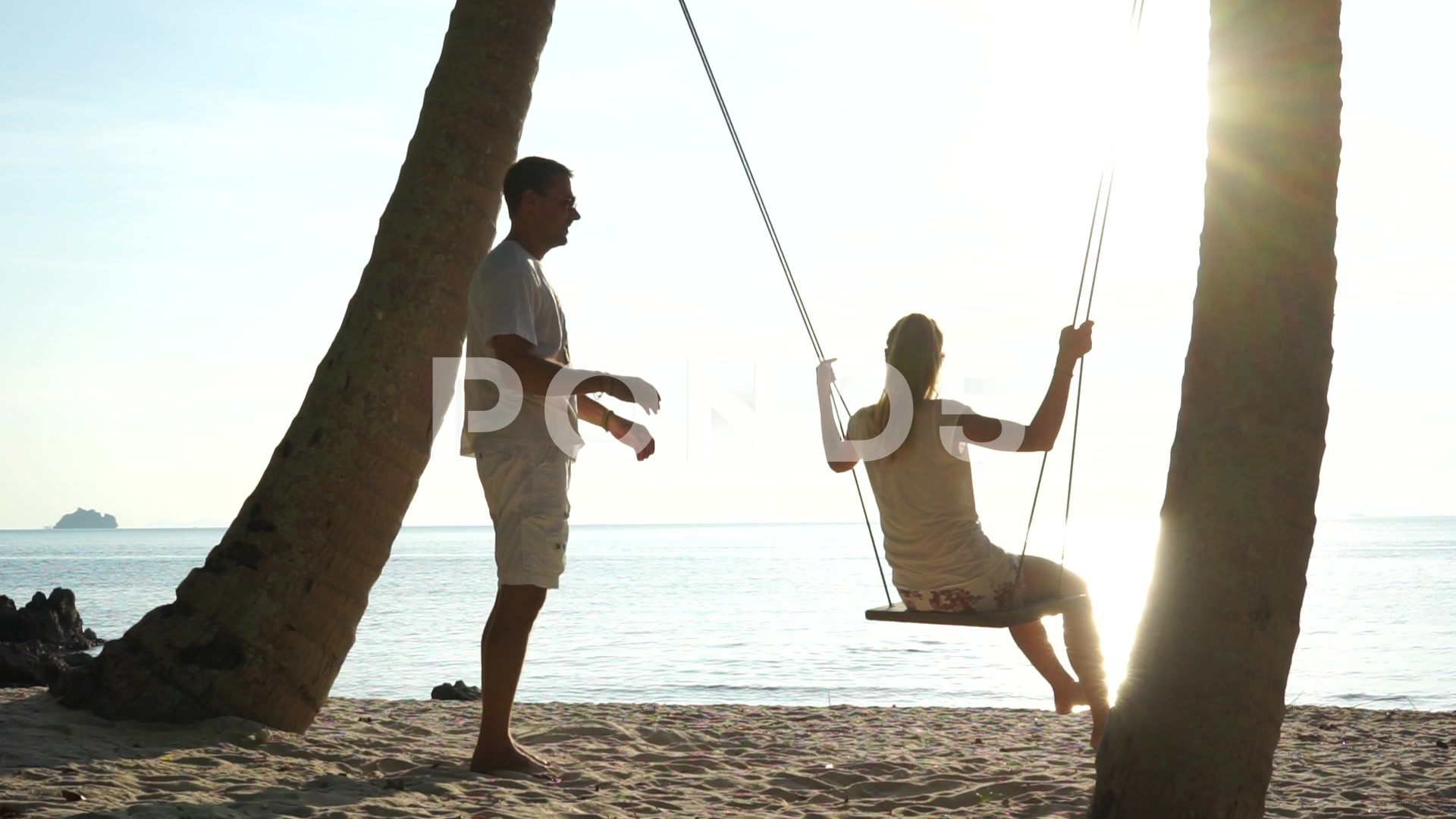 Young couple on a swing at the tropical beach against the sea ~ Clip ...