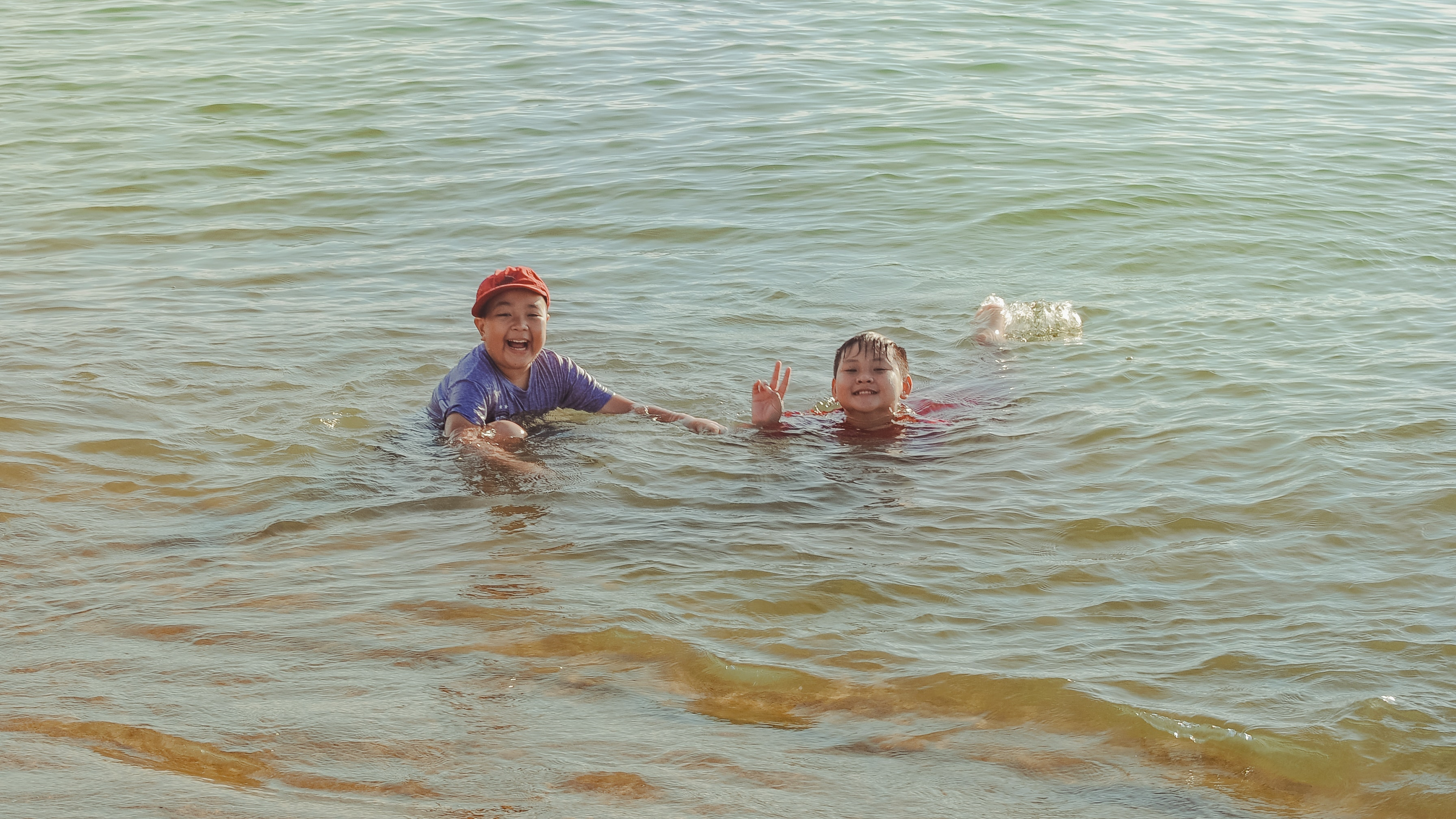 Two boy on brown body of water photo