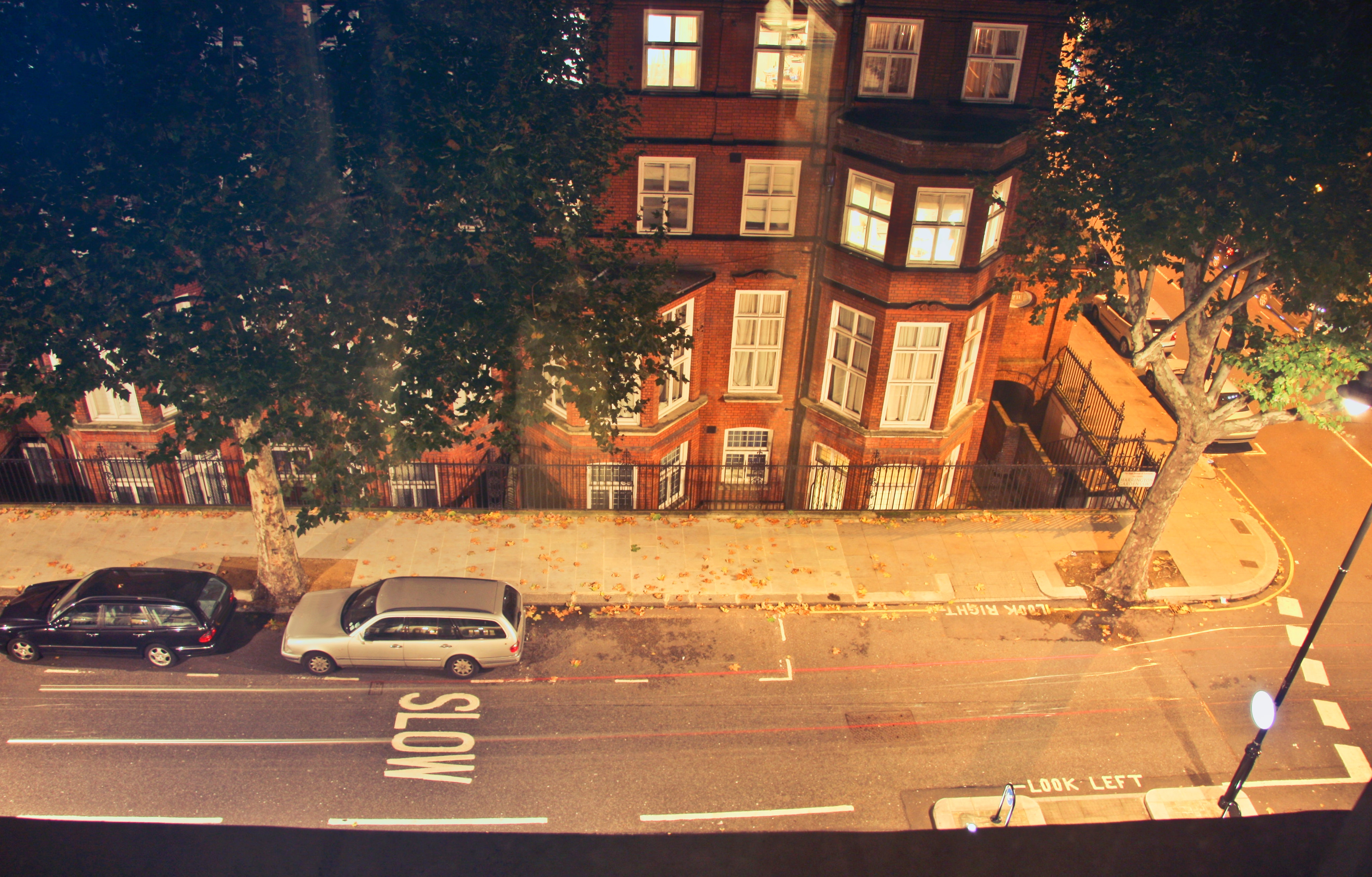 Two cars parked near brown concrete building during nighttime photo