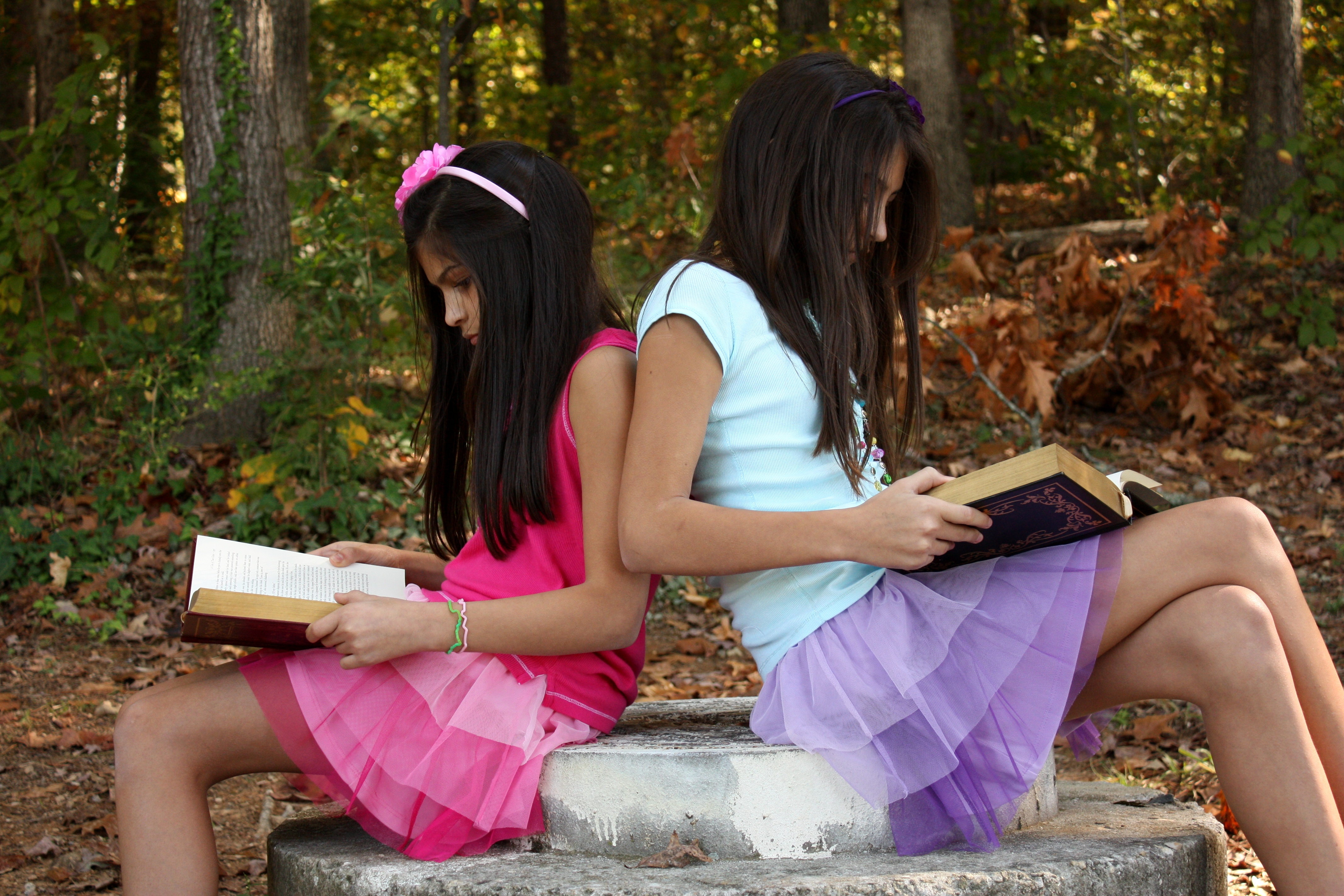 Two cute young girls reading books photo