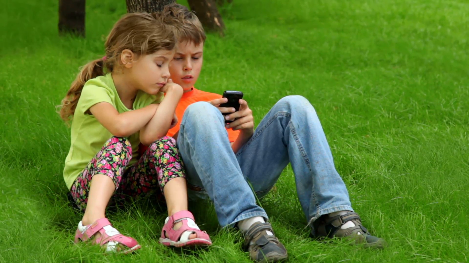 Two kids sit together, boy plays with digital game on cell phone ...