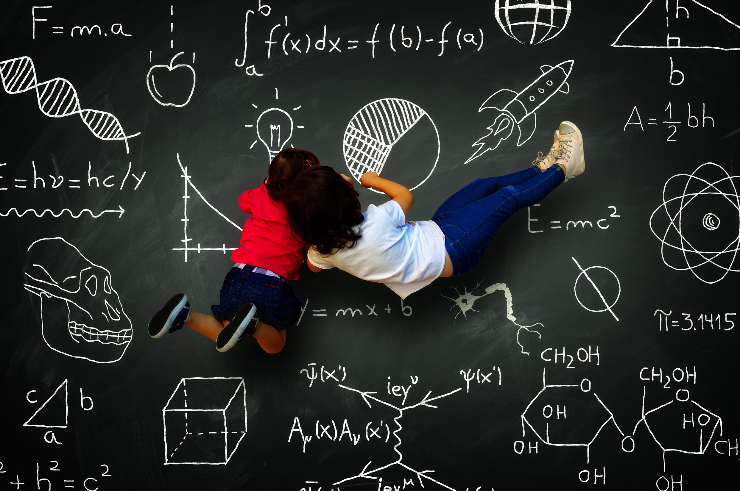 Two little girls writing on a blackboard with science subjects photo