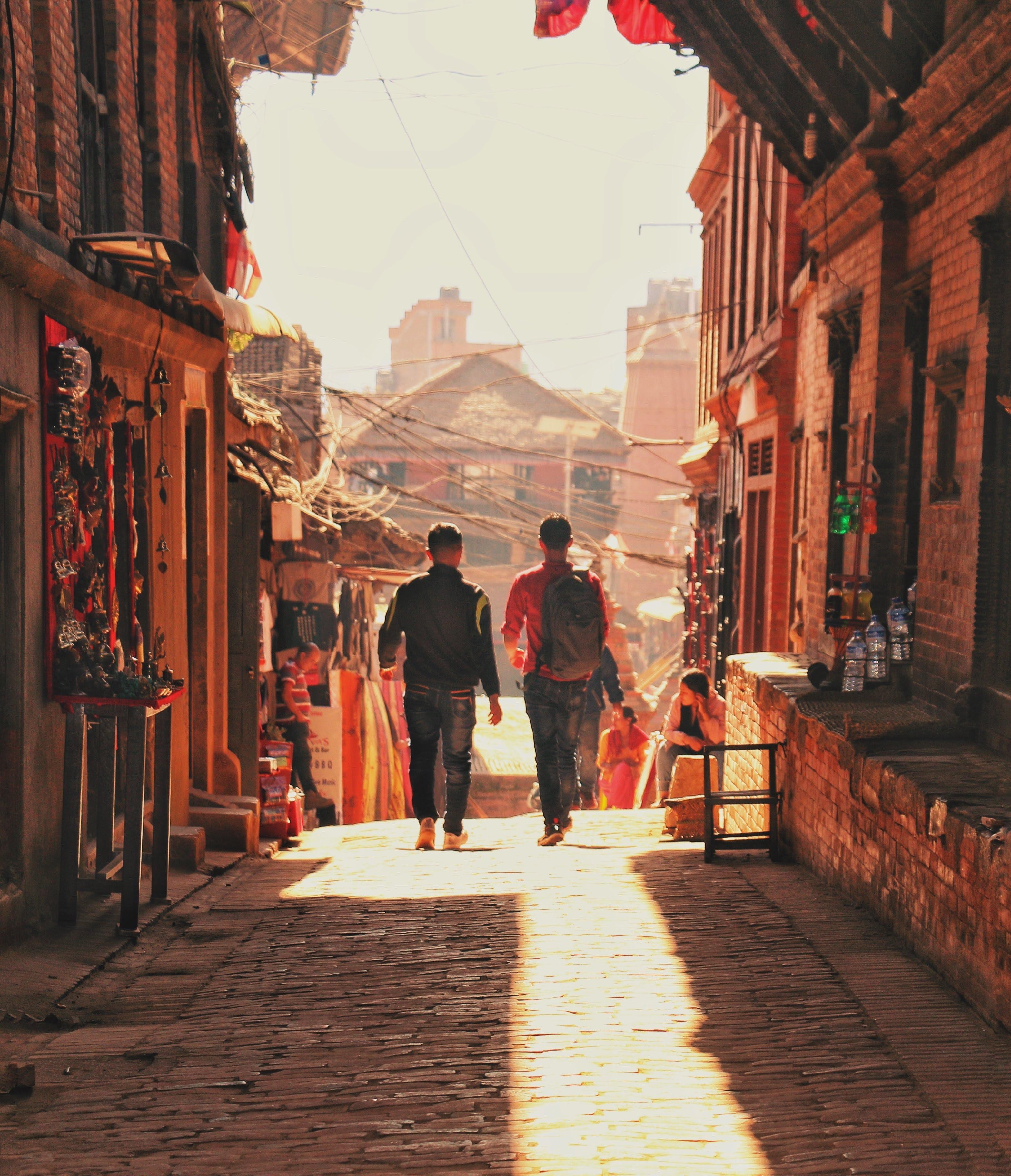 Two man walking beside brick houses photo