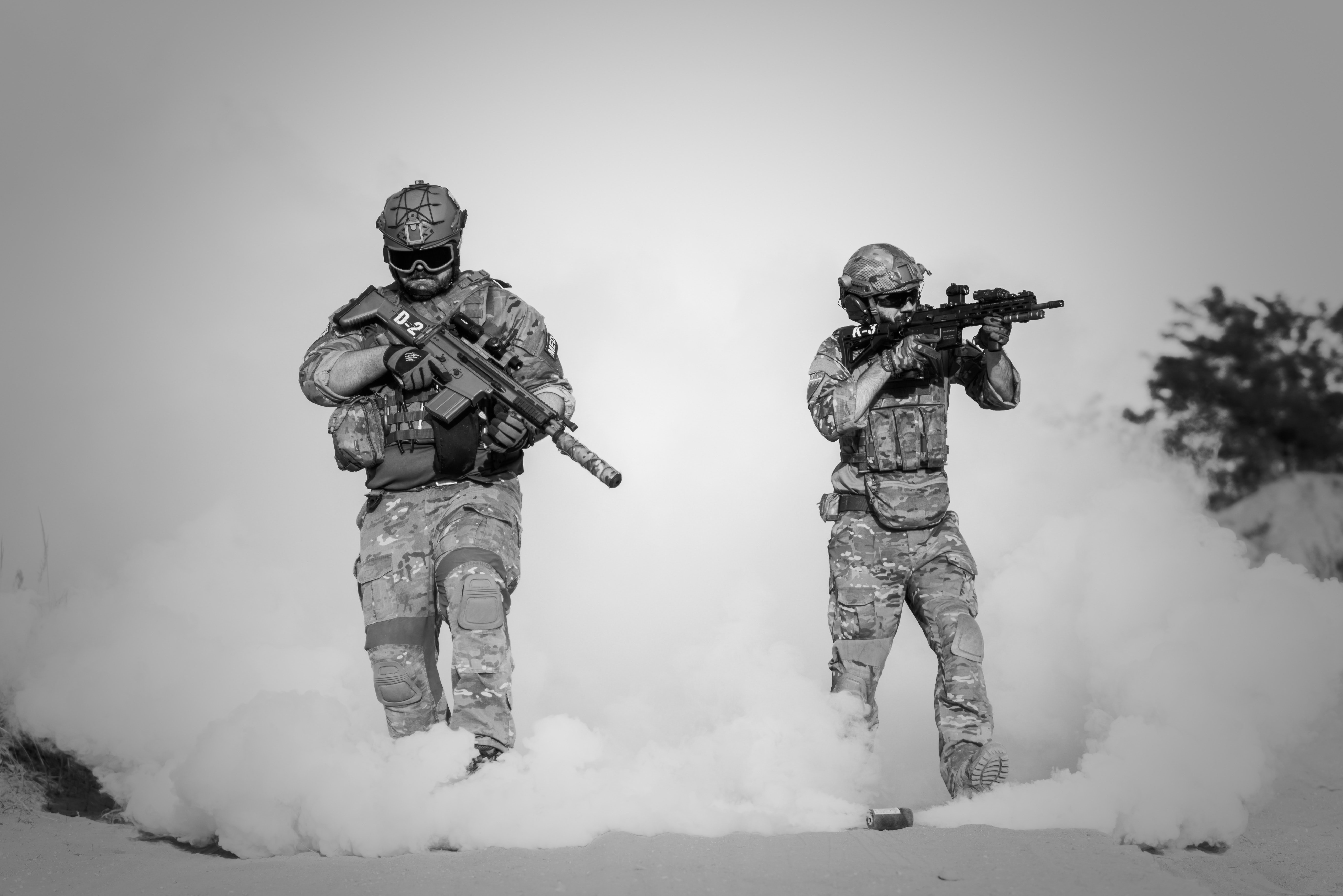 Two men in military clothing with guns photo