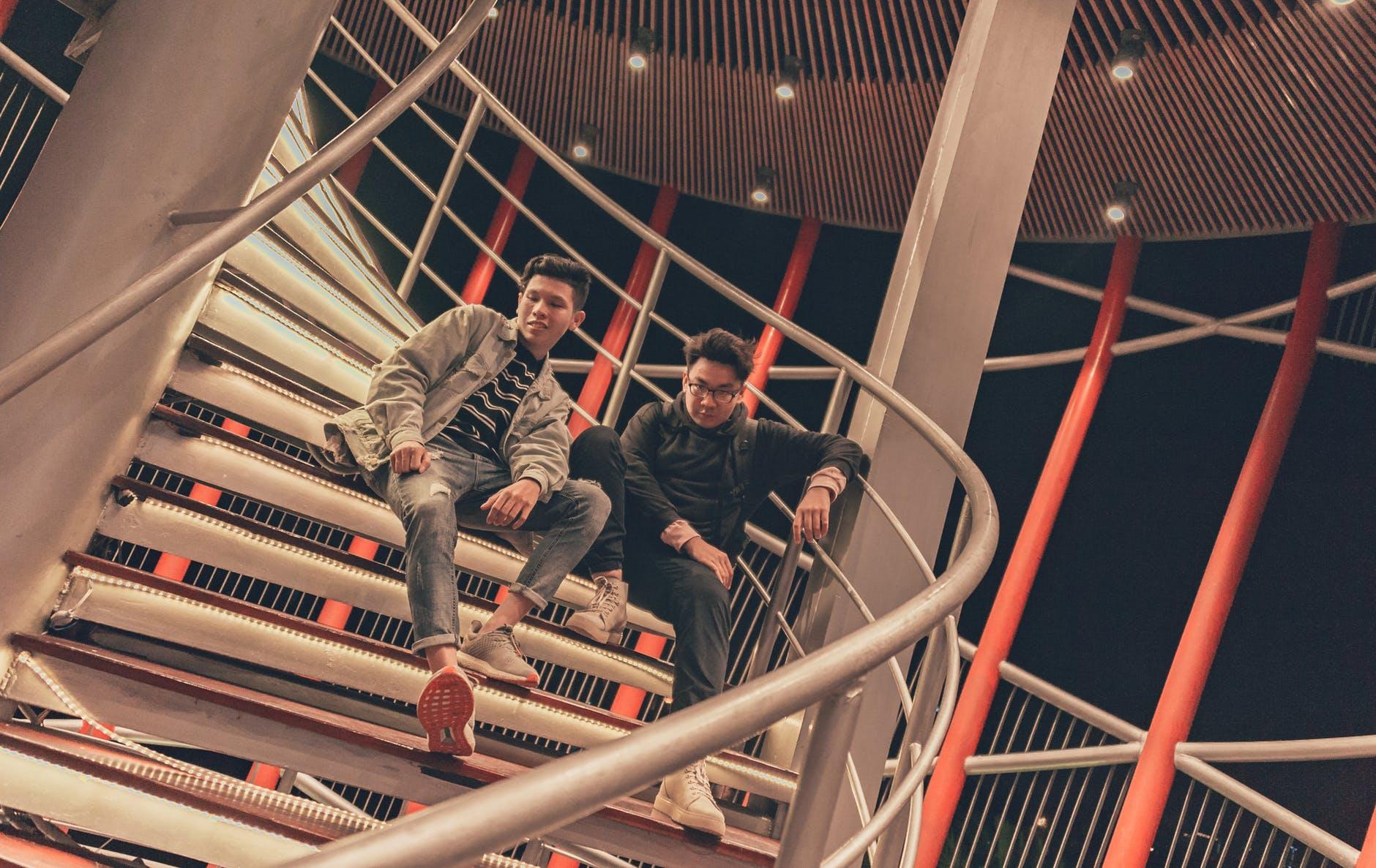 Two men sitting on spiral stairway photo